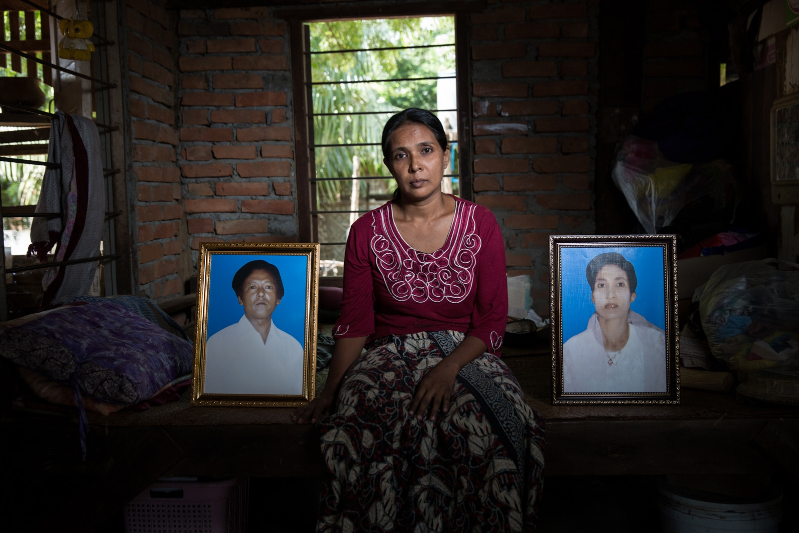 The daughter of arbitrarily detained U Kaung Shin and Daw Khin Thank Myint sits with the portraits of her mother and father in their house. Myanmar military intelligence arrested U Kaung Shin, 66, and Daw Khin Than Myint, 64, on their son's wedding day while they were en route to Kunhein, Shan State on August 4, 2014. On January 12, 2015 the Taunggyi District Court sentenced them in a trial that failed to meet fair trial standards to 14 years imprisonment with hard labor under the sections 5(J) and 5(L) of the 1950 Emergency Provisions Act. In October 2016, the Myanmar government repealed the notoriously controversial 1950 Emergency Provisions Act, yet U Kaung Shin, Daw Khin Than Myint, and others remain detained under the now defunct Act.