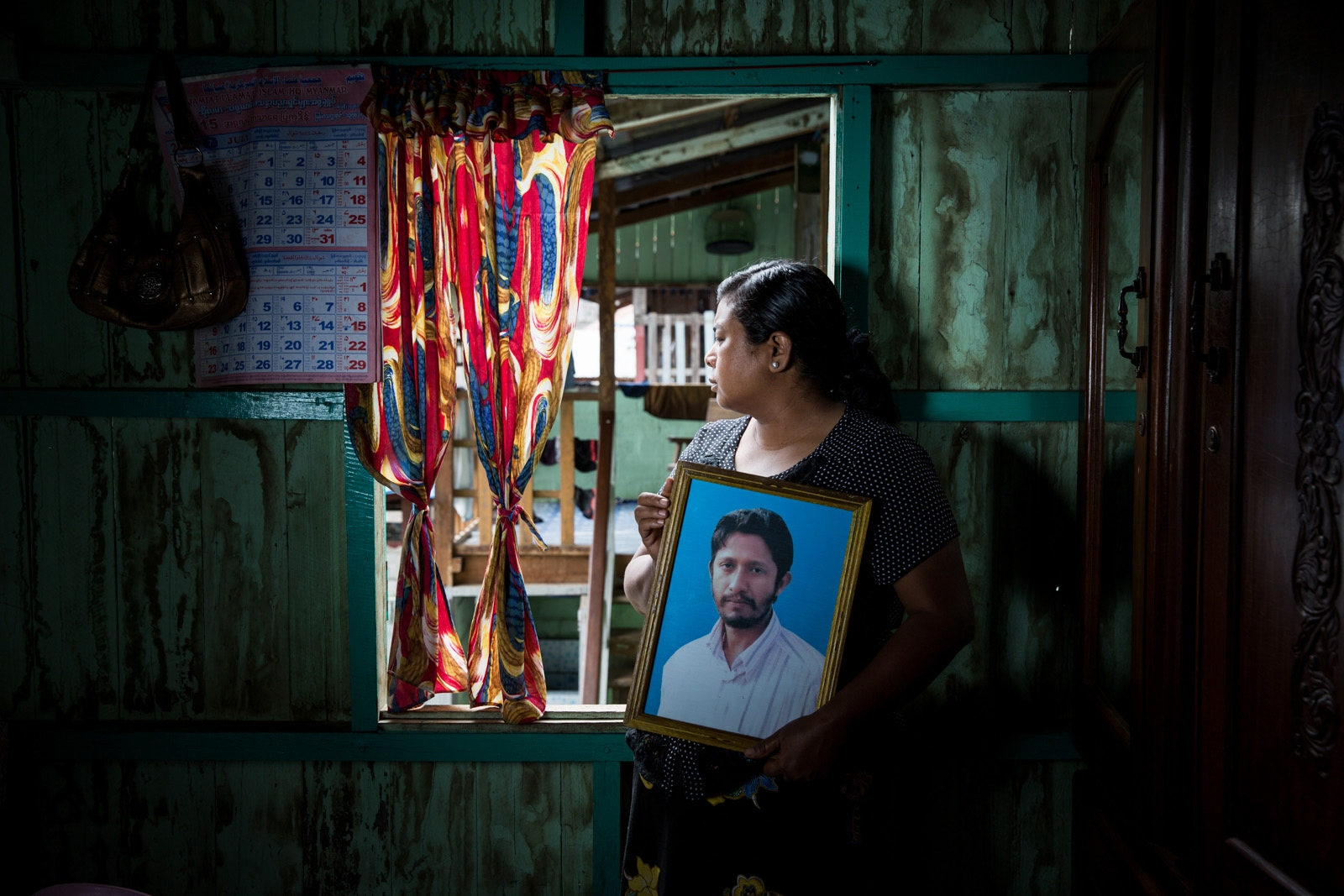 The wife of arbitrarily detained Htay Win holds his picture in their family house in Taungyi. Myanmar military intelligence arrested Htay Win, 44, at his home in Taunggyi in Shan State. He was beaten and arrested in front of his family. The Taunggyi District Court sentenced him in a trial that failed to meet fair trial standards to 14 years imprisonment with hard labor under the sections 5(J) and 5(L) of the 1950 Emergency Provisions Act. In October 2016, the Myanmar government repealed the notoriously controversial 1950 Emergency Provisions Act, yet Htay Win and others remain detained under the now defunct Act.