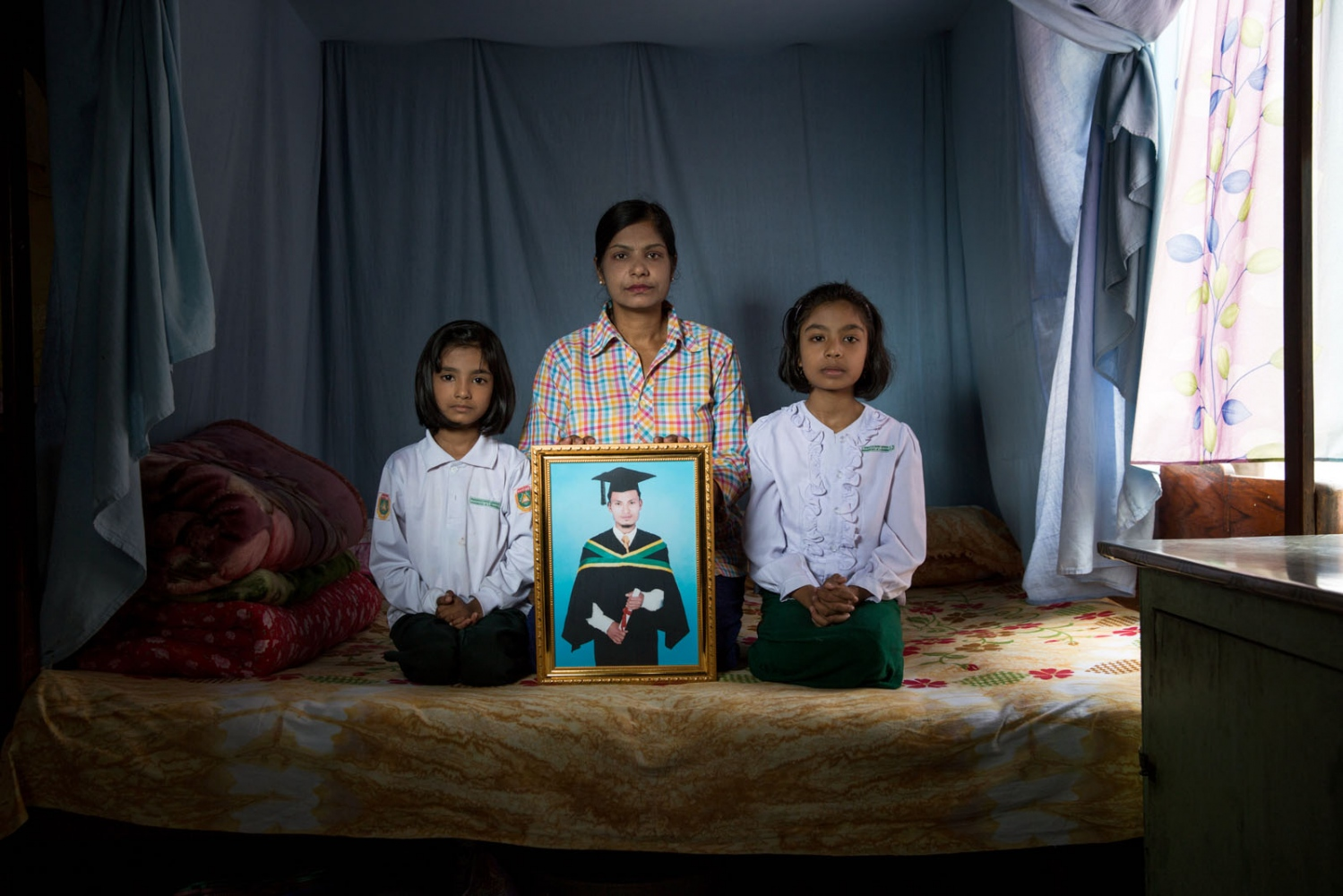 The wife and two daughters of arbitrarily detained Than Khaing hold his portrait in the family bed where they all sleep. Myanmar military intelligence arrested 32-year old Than Khaing, father of two, while he was traveling to attend the wedding of his friend Myo Myint Htun in Kunhein, Shan State on August 4, 2014.  The Taunggyi District Court sentenced him in a trial that failed to meet fair trial standards to 14 years' imprisonment with hard labor under the sections 5(J) and 5(L) of the 1950 Emergency Provisions Act. In October 2016, the Myanmar government repealed the notoriously controversial 1950 Emergency Provisions Act, yet Than Khaing and others remain detained under the now defunct Act.