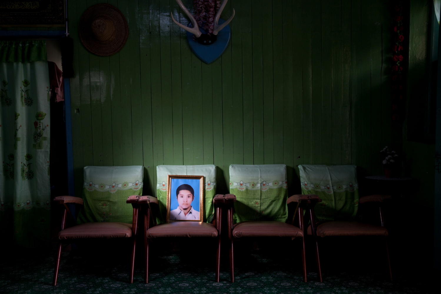 A portrait of Thant Zin Htwe, 25, in his families house. They were too frightened to be pictured in the picture for fear of retribution. Myanmar military intelligence arrested Thant Zin Htwe en route to a wedding in Kunhein, Shan State on August 4, 2014. On January 12, 2015, the Taunggyi District Court sentenced him in a trial that failed to meet fair trial standards to 14 years' imprisonment with hard labor under the sections 5(J) and 5(L) of the 1950 Emergency Provisions Act. In October 2016, the Myanmar government repealed the notoriously controversial 1950 Emergency Provisions Act, yet Thant Zin Htwe remains detained in Myaung Mya prison under the now defunct Act.""