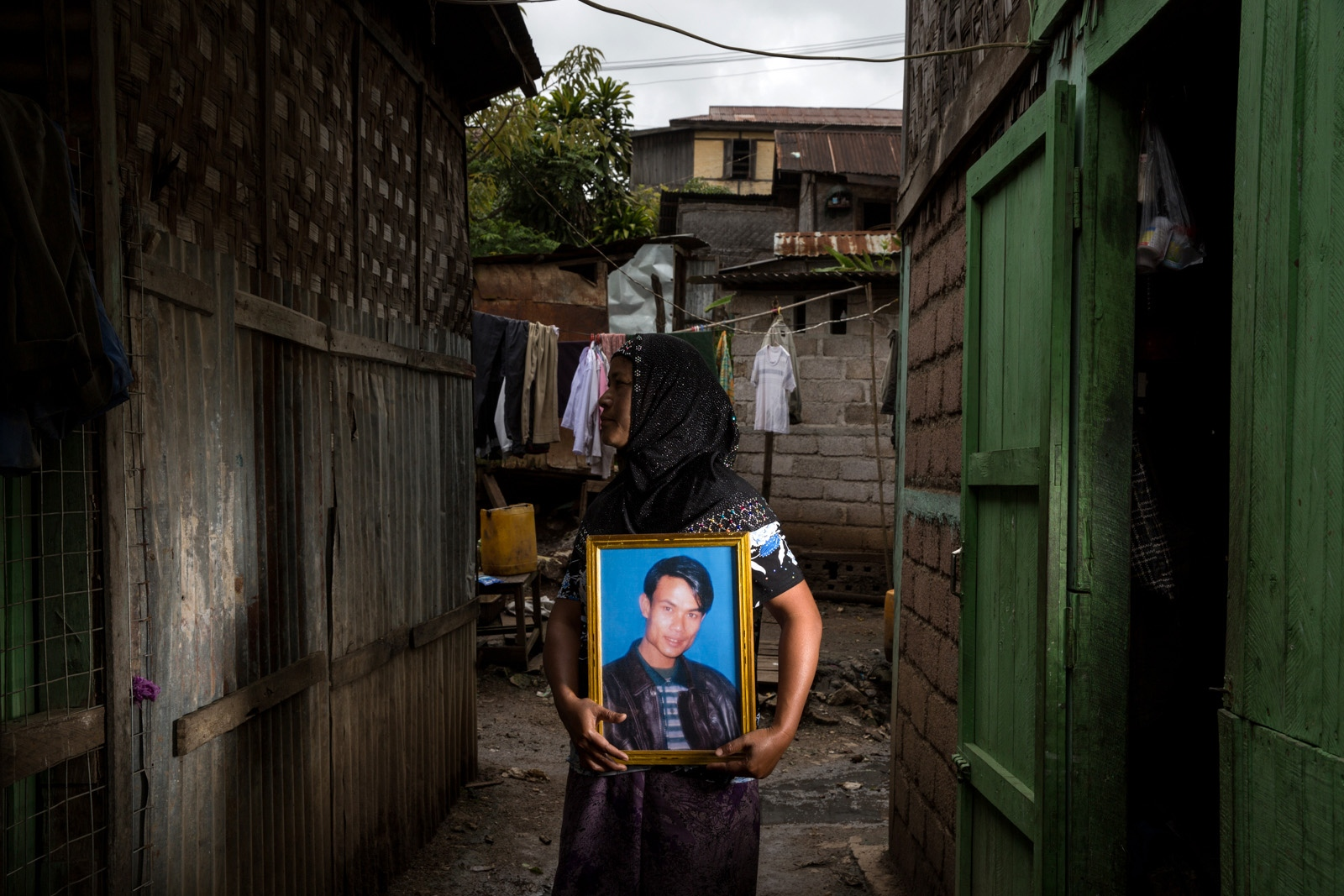 The wife of arbitrarily detained Myant Thu holds his portrait at their family home. She didn't want to show her face for fear of retribution. Myanmar military intelligence arrested Myat Thu, 39, who was traveling to Kunhein, Shan State on August 4, 2014 for the wedding of Aye Aye San and Myo Myint Htun. He was hired to cook for the wedding party.  The Taunggyi District Court sentenced him in a trial that failed to meet fair trial standards to 14 years imprisonment with hard labor under sections 5(J) and 5(L) of the 1950 Emergency Provisions Act.  In October 2016, the Myanmar government repealed the notoriously controversial 1950 Emergency Provisions Act, yet Myat Thu and others remain detained under the now defunct Act.