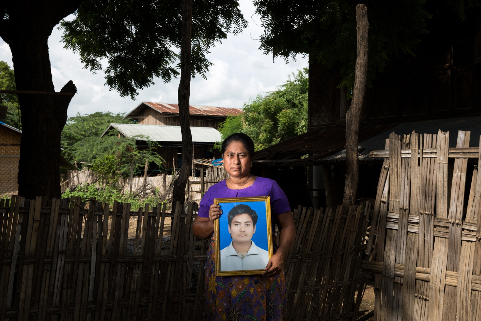 """Mother of arbitrarily detained Ye Ko, 24, holds her son's portrait. Special Branch officers arrested Ye Ko at a checkpoint near Lashio in northern Shan State on November 14, 2014 for allegedly establishing the """"Myanmar Muslim Army."""" Despite the government's failure to present evidence of the existence of the Myanmar Muslim Army or Ye Ko's connection to the group, on December 7, 2015, the Aung Myay Tharsan Township Court in Mandalay Region sentenced Ye Ko to five years in prison under Section 5(J) of the 1950 Emergency Provisions Act. In October 2016, the Myanmar government repealed the notoriously controversial 1950 Emergency Provisions Act, yet Ye Ko remained detained in Mandalay Obo prison under the now defunct Act."""