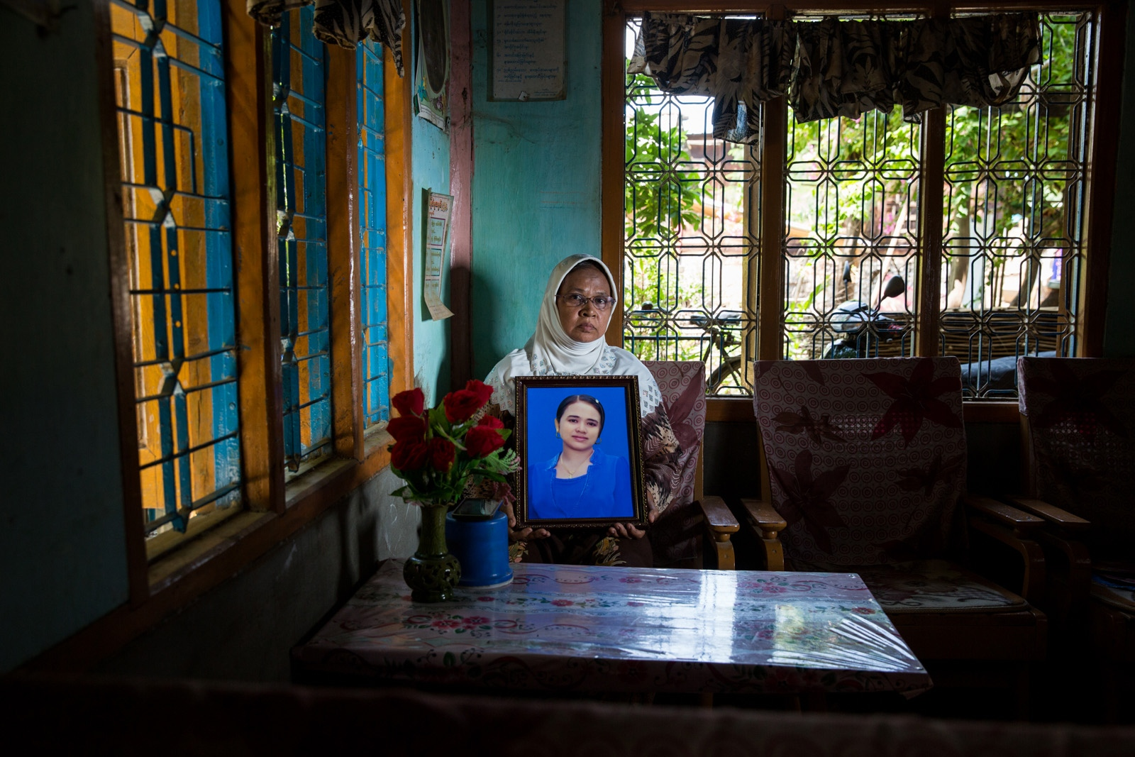 Arbitrarily detained Phyu Phy Khaing's adopted mother holds her daughter's portrait. Myanmar military intelligence arrested Phyu Phyu Khaing, 26, while she was traveling with her family to attend her brother's wedding in Kunhein, Shan State on August 4, 2014. The Taunggyi District Court sentenced her in a trial that failed to meet fair trial standards to 14 years' imprisonment with hard labor under sections 5(J) and 5(L) of the 1950 Emergency Provisions Act. In October 2016, the Myanmar government repealed the notoriously controversial 1950 Emergency Provisions Act, yet Phyu Phyu Khaing and others remain detained under the now defunct Act.