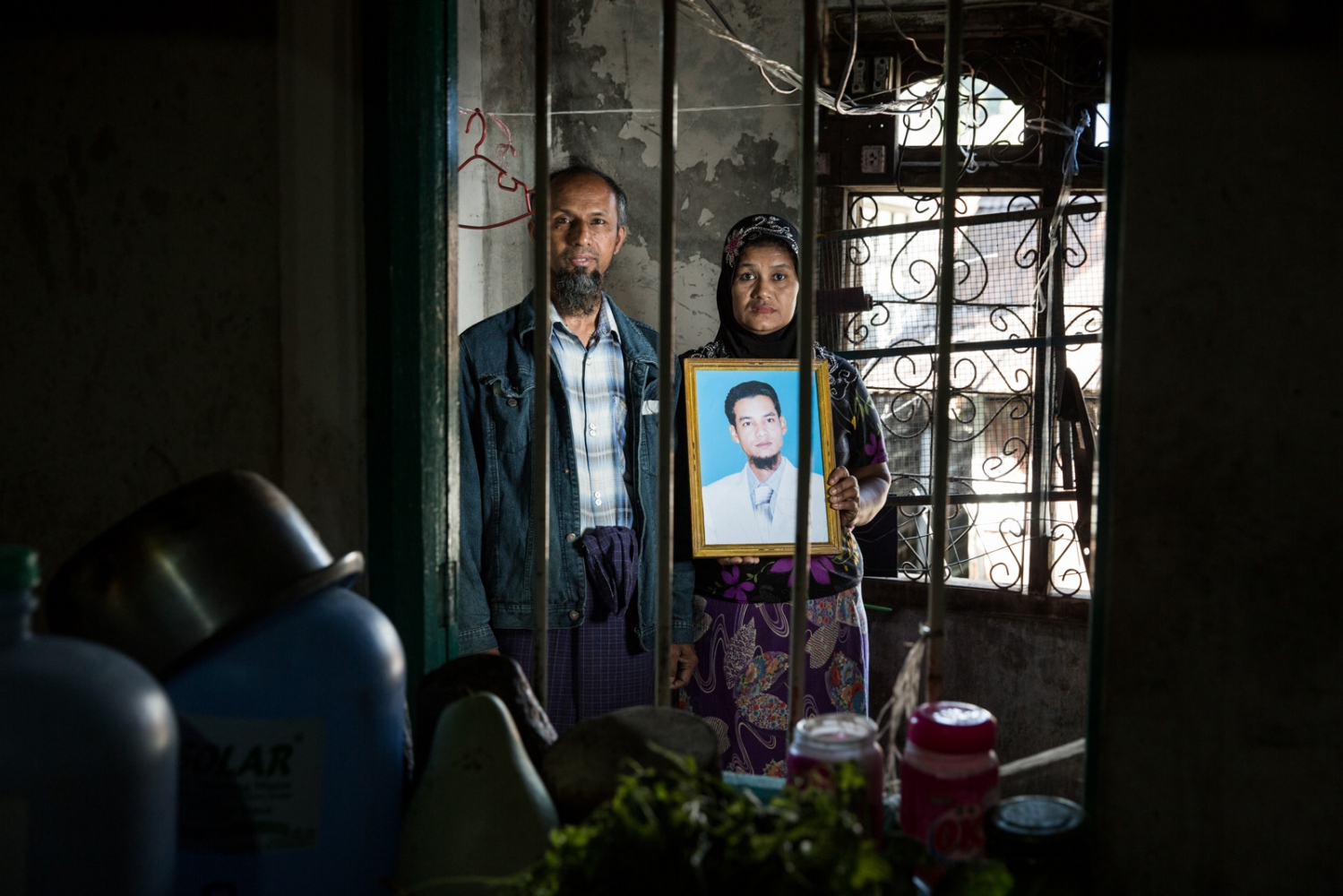 The father and mother of Naung Naung hold a portrait of their arbitrarily detained son. Myanmar military intelligence arrested Naung Naung, 26, while he was driving a taxi for his friend's wedding in Kunhein, Shan State on August 4, 2014.  The Taunggyi District Court sentenced him in a trial that failed to meet fair trial standards to 14 years' imprisonment with hard labor under sections 5(J) and 5(L) of the 1950 Emergency Provisions Act.  In October 2016, the Myanmar government repealed the notoriously controversial 1950 Emergency Provisions Act, yet Naung Naung and others remain detained under the now defunct Act.