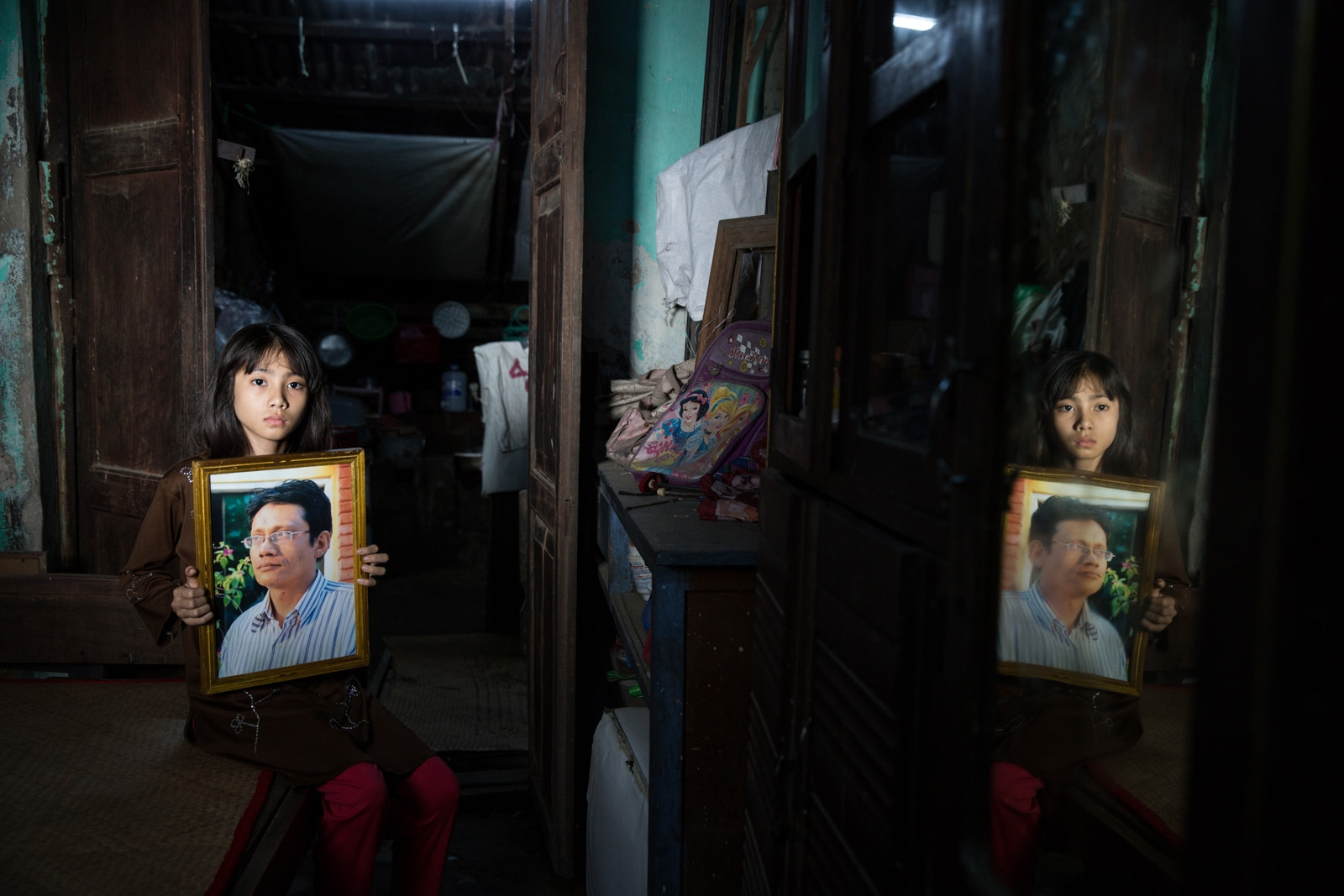 "Daughter of arbitrarily detained Zaw Min Htwe, 41, holds her father's portrait at the back of their family shop. Myanmar military intelligence arrested Zaw Min Htwe, who is an artist, at his home in Mandalay on August 21, 2014 while he was drinking his tea. The military intelligence officers told his spouse and daughters that they would ""return him before his tea get cold."" According to documents submitted to the court, the Military Intelligence officers interrogated him continuously for seven days and deprived him of sleep, water, and food. On November 29, 2016, the Amarapura Township Court in Mandalay sentenced Zaw Min Htwe to five years' imprisonment with hard labor under section 5(L) of the Emergency Provisions Act and Section 505(C) of the Myanmar Penal Code. On December 20, the Mandalay Township Court sentenced him to an additional three years' imprisonment under Section 17(1) of the Unlawful Associations Act. Two days later, on December 22, the Mandalay District Court imposed a life sentence on him for high treason under Section 122 of the Myanmar Penal Code and an additional sentence of seven years' imprisonment for alleged violations of Section 52(a) of the Counterterrorism Law on December 28. The sentences relate to accusations that Zaw Min Htwe carried out the Islamic militant activities in Myanmar, despite the government's failure to present evidence of the Zaw Min Htwe's connection to the militant group. Zaw Min Htwe is currently detained in Mandalay Obo prison."