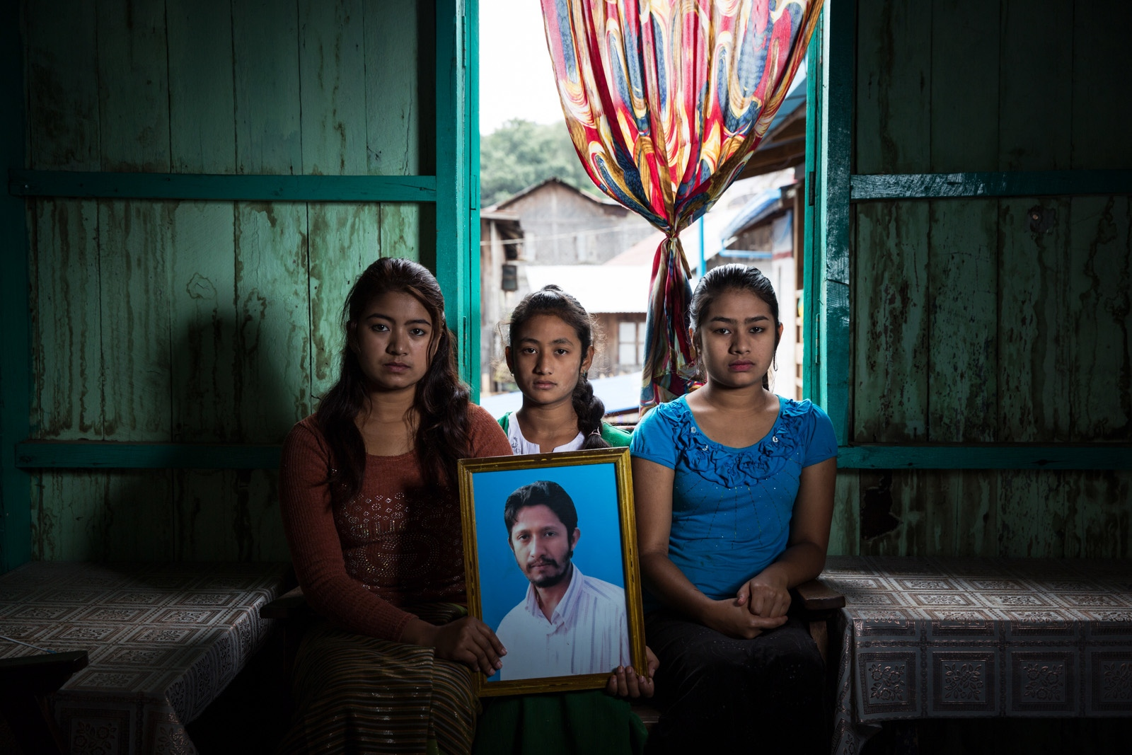 Three daughters hold the portrait of their arbitrarily detained father Htay Win. Myanmar military intelligence arrested Htay Win, 44, at his home in Taunggyi in Shan State. He was beaten and arrested in front of his family. The Taunggyi District Court sentenced him in a trial that failed to meet fair trial standards to 14 years' imprisonment with hard labor under sections 5(J) and 5(L) of the 1950 Emergency Provisions Act. In October 2016, the Myanmar government repealed the notoriously controversial 1950 Emergency Provisions Act, yet Htay Win and others remain detained under the now defunct Act.