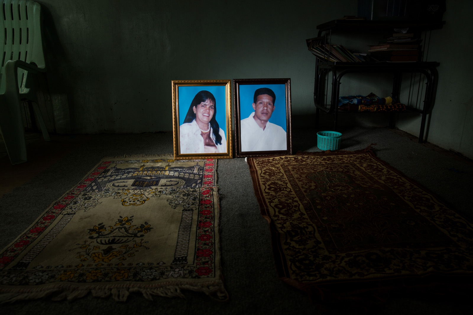 U Khin Maung Oo, 52, and Daw Khaing Khaing, 54, were hired to cook at a wedding in Kunhein, Shan State on August 4, 2014. Here their photographs are placed on the families prayer mats. On the way to the wedding, the Myanmar military intelligence arrested them. No-one from their family wanted to be in the photograph for fear of retribution. On January 12, 2015 the Taunggyi District Court sentenced them in a trial that failed to meet fair trial standards to 14 years' imprisonment with hard labor under the sections 5(J) and 5(L) of the 1950 Emergency Provisions Act. In October 2016, the Myanmar government repealed the notoriously controversial 1950 Emergency Provisions Act, yet U Khin Maung Oo, Daw Khaing Khaing, and others remain detained under the now defunct Act.