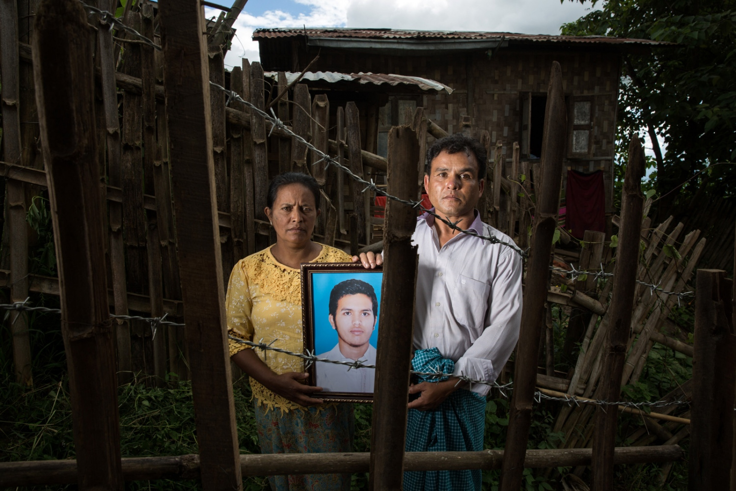 Arbitrarily detained Sithu Hein's father and mother hold a portrait of their son outside their family home. Myanmar military intelligence arrested Sithu Hein, 19, en route to a wedding in Kunhein, Shan State on August 4, 2014.  The Taunggyi District Court sentenced him in a trial that failed to meet fair trial standards to 14 years' imprisonment with hard labor under the sections 5(J) and 5(L) of the 1950 Emergency Provisions Act. In October 2016, the Myanmar government repealed the notoriously controversial 1950 Emergency Provisions Act, yet Sithu Hein and others remain detained under the now defunct Act. In October 2016, the Myanmar government repealed the notoriously controversial 1950 Emergency Provisions Act, yet Sithu Hein and others remain detained under the now defunct Act.