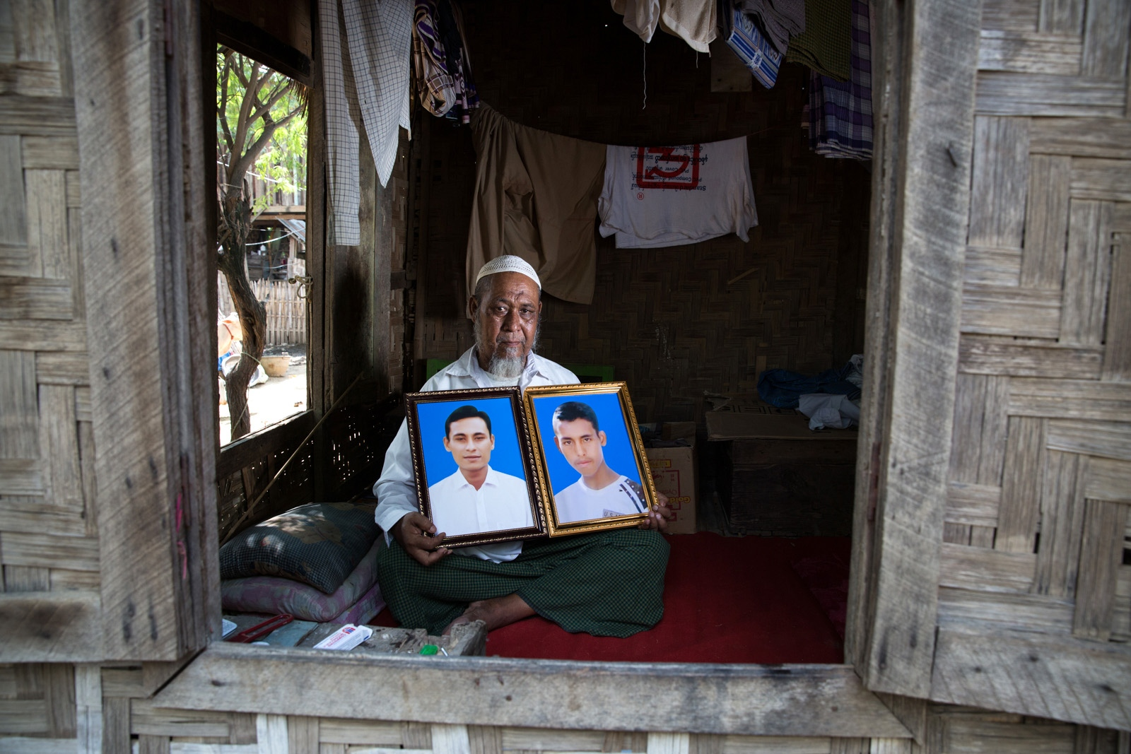 "The father of Tin Oo, 19, (Right) and Maung Maung Min Ko, 36, (Left) holds her sons' portraits. Special Branch officers arrested Tin Oo and his brother Maung Maung Min Ko at a checkpoint near Lashio in northern Shan State on November 14, 2014 for allegedly establishing the ""Myanmar Muslim Army."" Despite the government's failure to present evidence of the existence of the Myanmar Muslim Army or Tin Oo and Maung Muang Min Ko's connection to the group, on December 7, 2015, the Aung Myay Tharsan Township Court in Mandalay Region sentenced the two brothers to five years in prison for allegedly violating section 5(J) of the 1950 Emergency Provisions Act.  In 2017, the Myanmar authorities released Maung Maung Min Ko under a presidential amnesty. Tin Oo remains detained at Mandalay Obo prison."