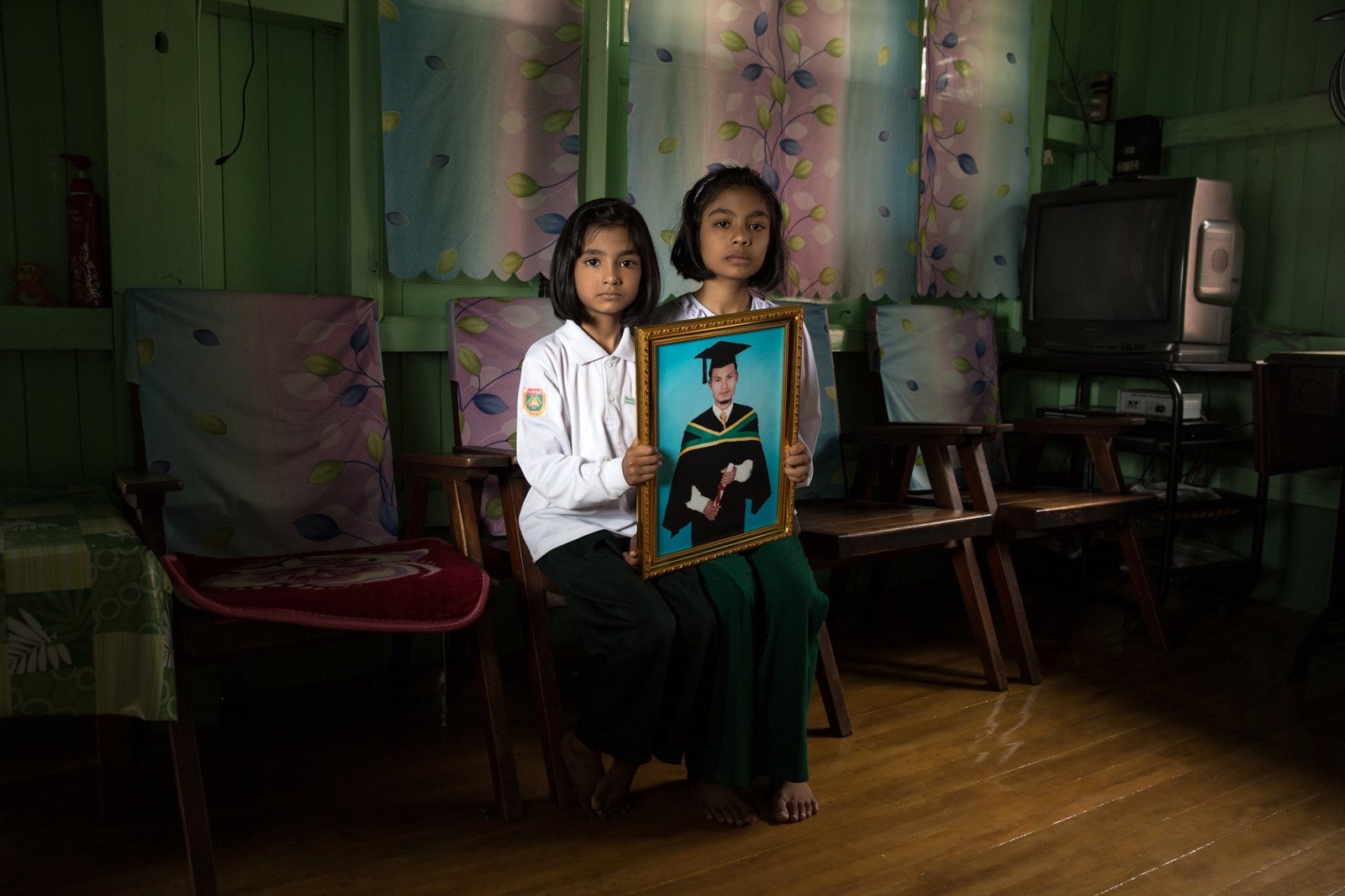 The two daughters of arbitrarily detained Than Khaing hold his portrait in their house in Taungyi town. Myanmar military intelligence arrested 32-year old Than Khaing while he was traveling to attend the wedding of his friend Myo Myint Htun in Kunhein, Shan State on August 4, 2014.  The Taunggyi District Court sentenced him in a trial that failed to meet fair trial standards to 14 years imprisonment with hard labor under the sections 5(J) and 5(L) of the 1950 Emergency Provisions Act.  In October 2016, the Myanmar government repealed the notoriously controversial 1950 Emergency Provisions Act, yet Than Khaing and others remain detained under the now defunct Act and should be released.