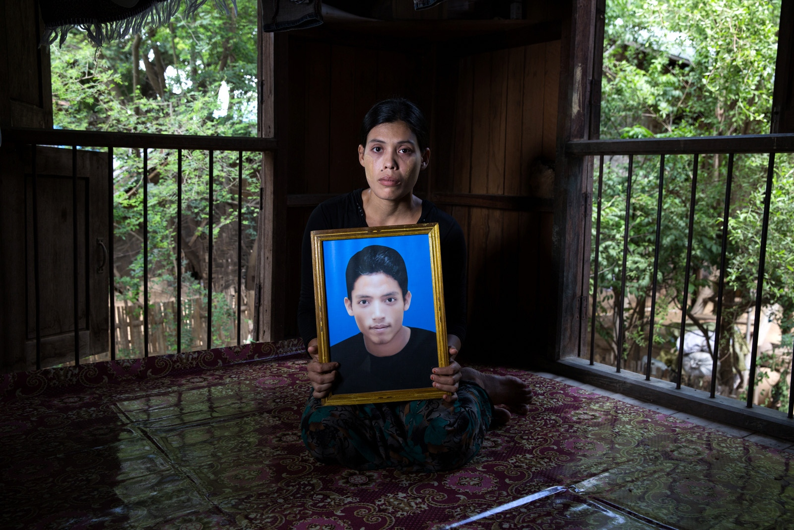 "The wife of arbitrarily detained Ko Ko Naing, 21, holds her husband's portrait in their family home. Special Branch officers arrested Ko Ko Naing at a checkpoint near Lashio in northern Shan State on November 14, 2014 for allegedly establishing the ""Myanmar Muslim Army."" Despite the government's failure to present evidence of the existence of the Myanmar Muslim Army or Ko Ko Naing's connection to the group, on December 7, 2015, the Aung Myay Tharsan Township Court in Mandalay Region sentenced Ko Ko Naing to five years in prison under Section 5(J) of the 1950 Emergency Provisions Act. In October 2016, the Myanmar government repealed the notoriously controversial 1950 Emergency Provisions Act, yet Ko Ko Naing remains detained in Mandalay Obo prison under the now defunct Act."