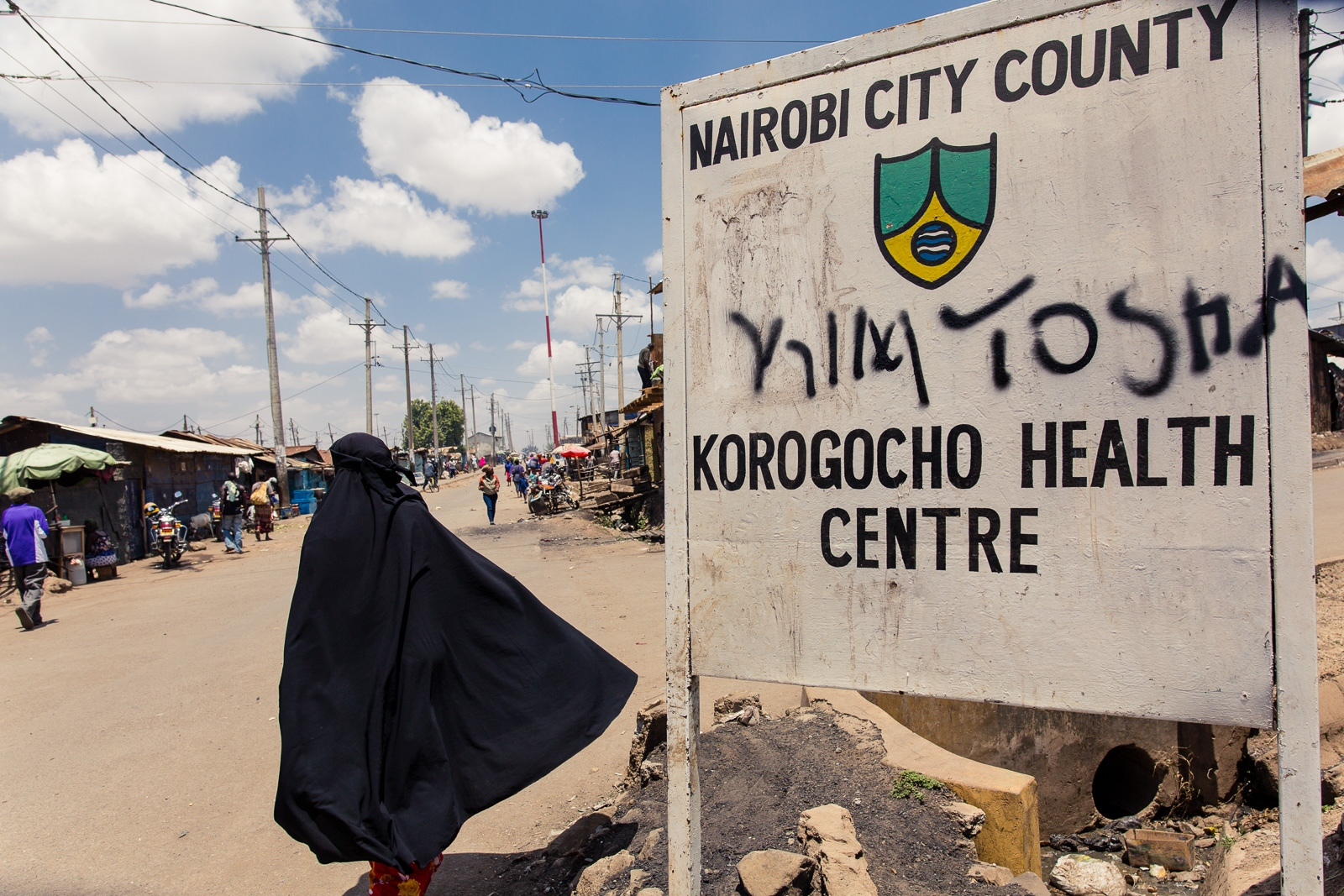 Nairobi, KENYA, February 28, 2017: A woman walks along a street in the Korogocho township, where elderly ladies have been a target of sexual violence, as a superstition persists, which says that having sex with a grandmother will cure one from HIV and wash off all criminal sins.