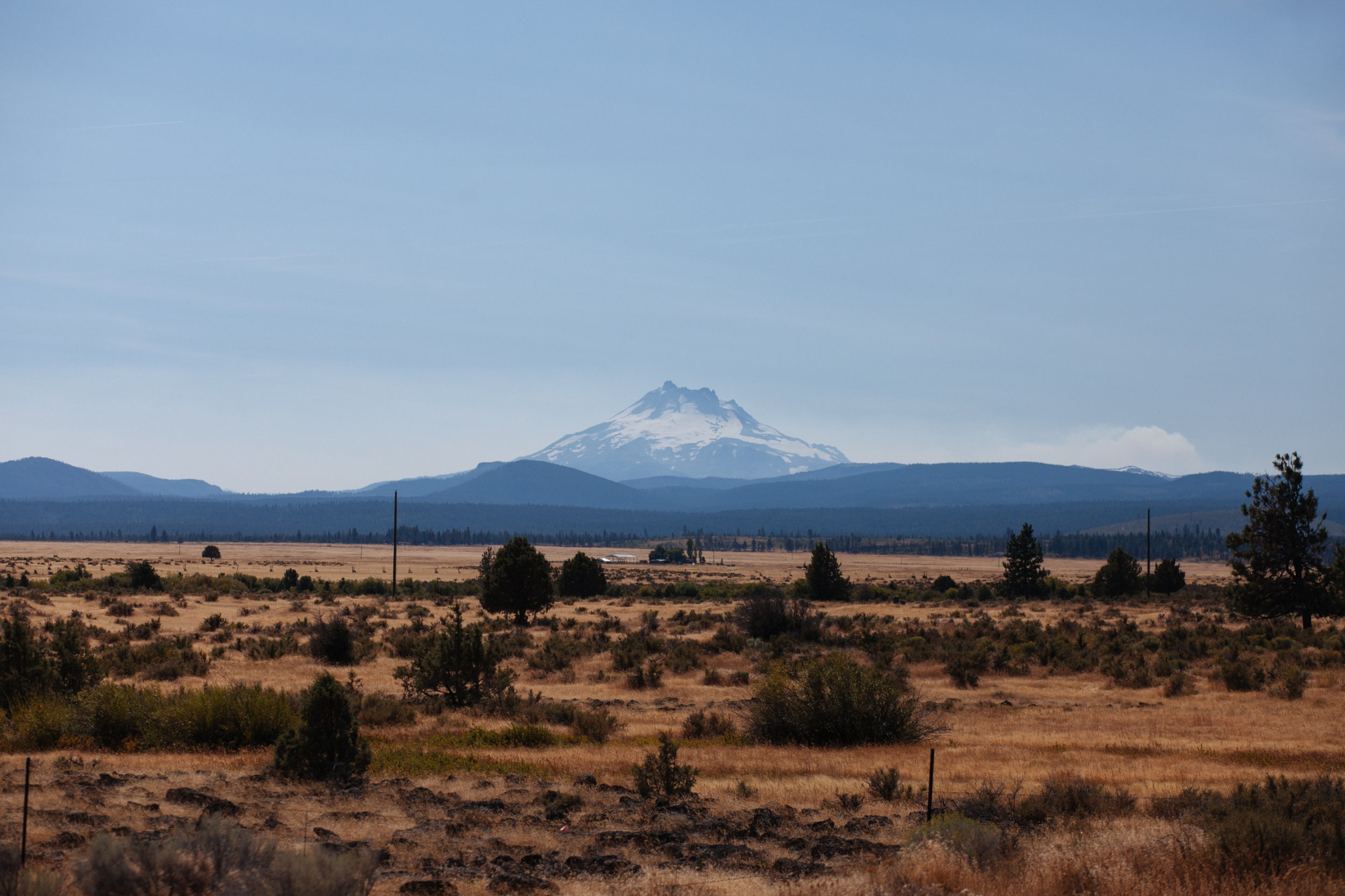 A view of Mount Jefferson behind Warm Springs Reservation, US 26, Oregon; As we drove down US 97 our windows are filled with images of Mt. Hood in the rear view and Mt. Jefferson in my passenger window. The air and clouds had a slight haze to them due to the forests burning in the distance. With only a couple of miles left between us and the flames we made our way down to Bend, Oregon.