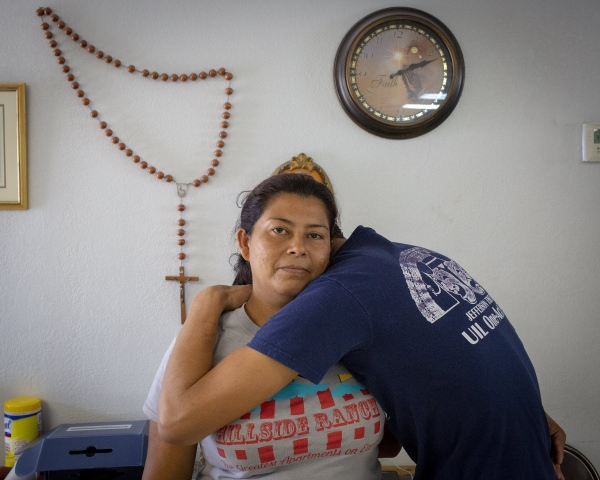 A woman from Central America holds her 16-year old son at a refugee center in McAllen TX. She told me that God told her to come to the United States. Nothing happened to her and her son. She believes that God was watching over them on their journey. (Kevin C Downs/Agence Cosmos)