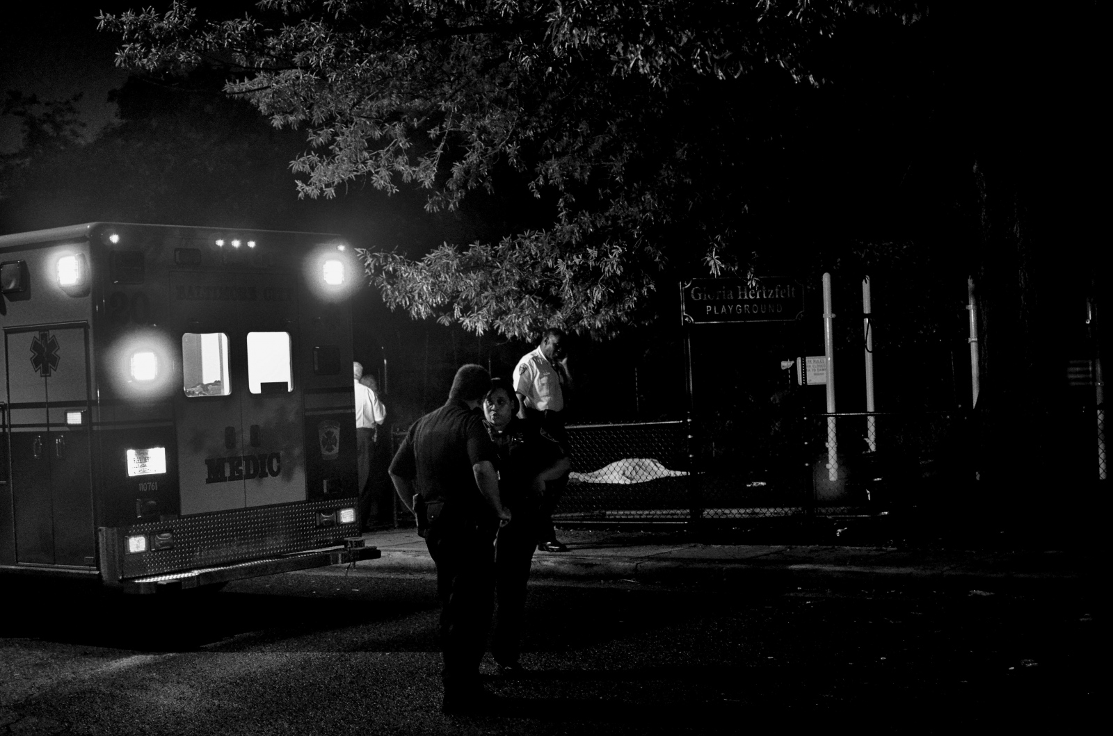 "Detectives and emergency officers at the scene of an ""execution"" in E. Baltimore's Greektown neighborhood. Police said that the man was shot in front of his girlfriend at the playground. Greektown is a traditionally quiet neighborhood. This was one of the rare shootings in the city's Latino/Latinex community. July 13, 2013."