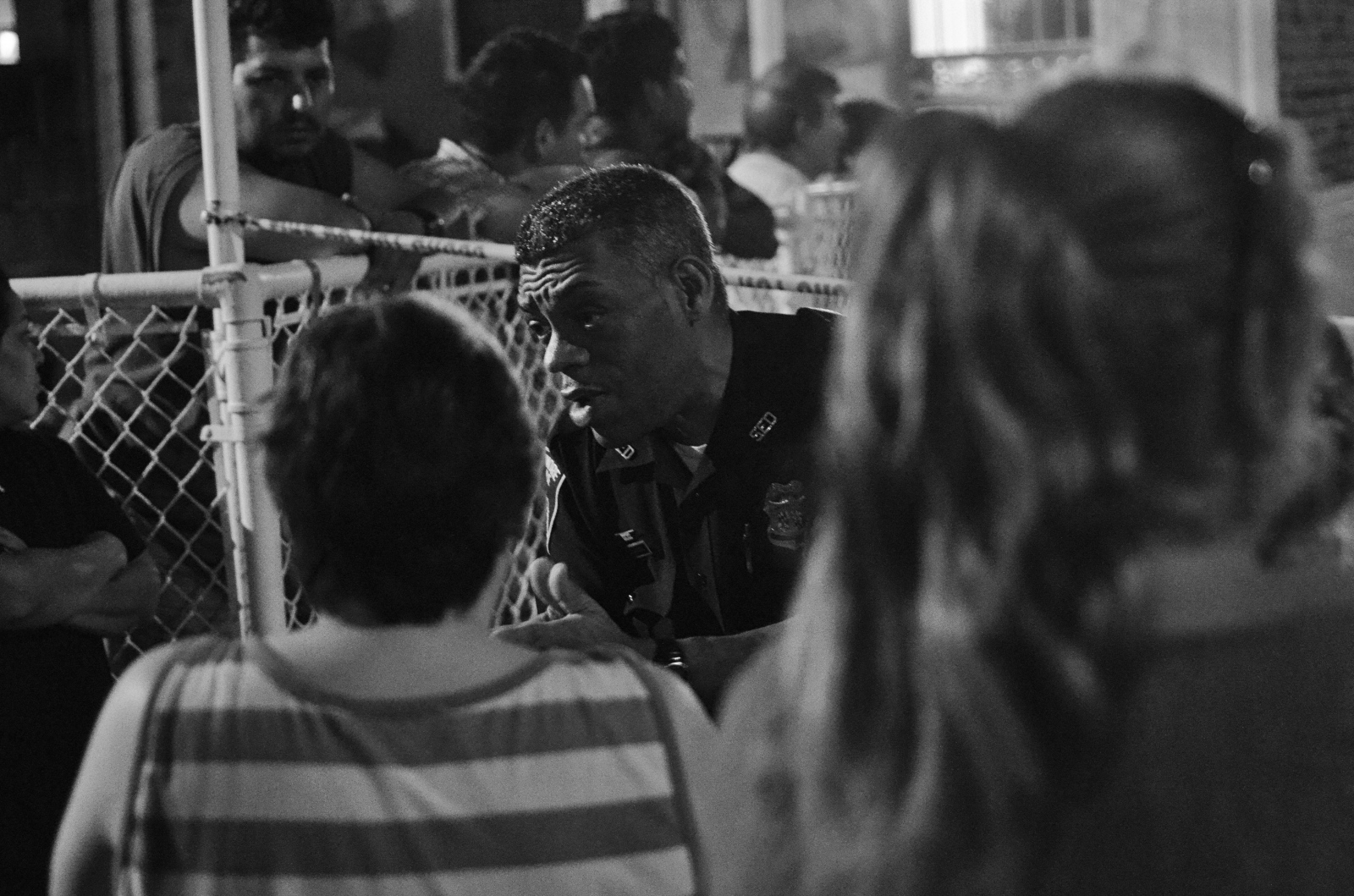 "An exhausted Baltimore City Police officer trys to calm the crowd at the scene of an ""execution"" in E. Baltimore's Greektown neighborhood. Police said that the man was shot in front of his girlfriend at the playground. Greektown is a traditionally quiet neighborhood. July 13, 2013, Gough and Lehigh streets."