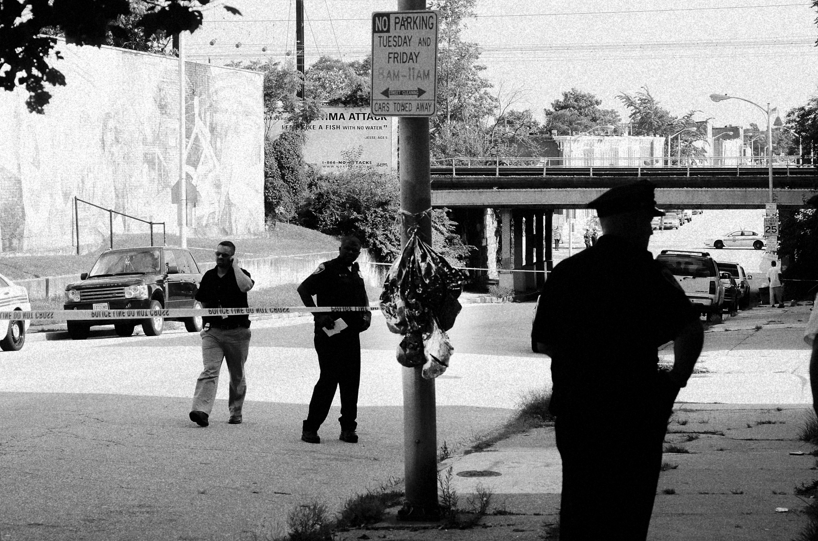 Police and detectives at a shooting scene in the 1000 block of Patterson Park Ave in E. Baltimore on July 22, 2013. The balloons are a memorial to another homicide that occurred there a month earlier.