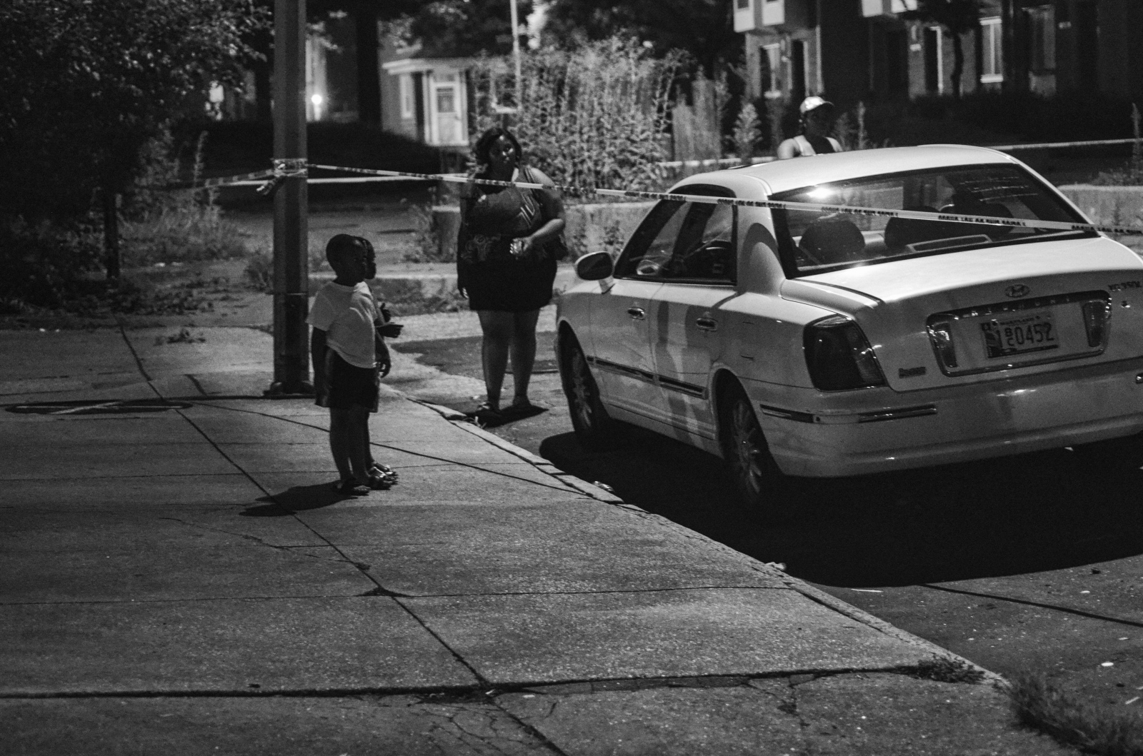 A child stops to look at a car involved in a late night shooting in the 1400 block of Ashland Avenue on July 28, 2013.