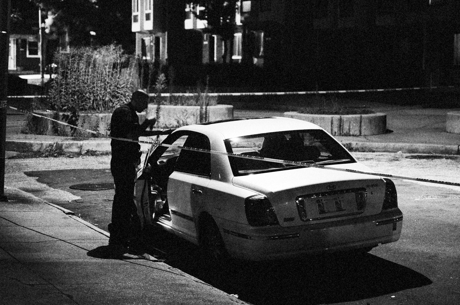 A police officer examines a car involved in a late night shooting in the 1400 block of Ashland Avenue on July 28, 2013.
