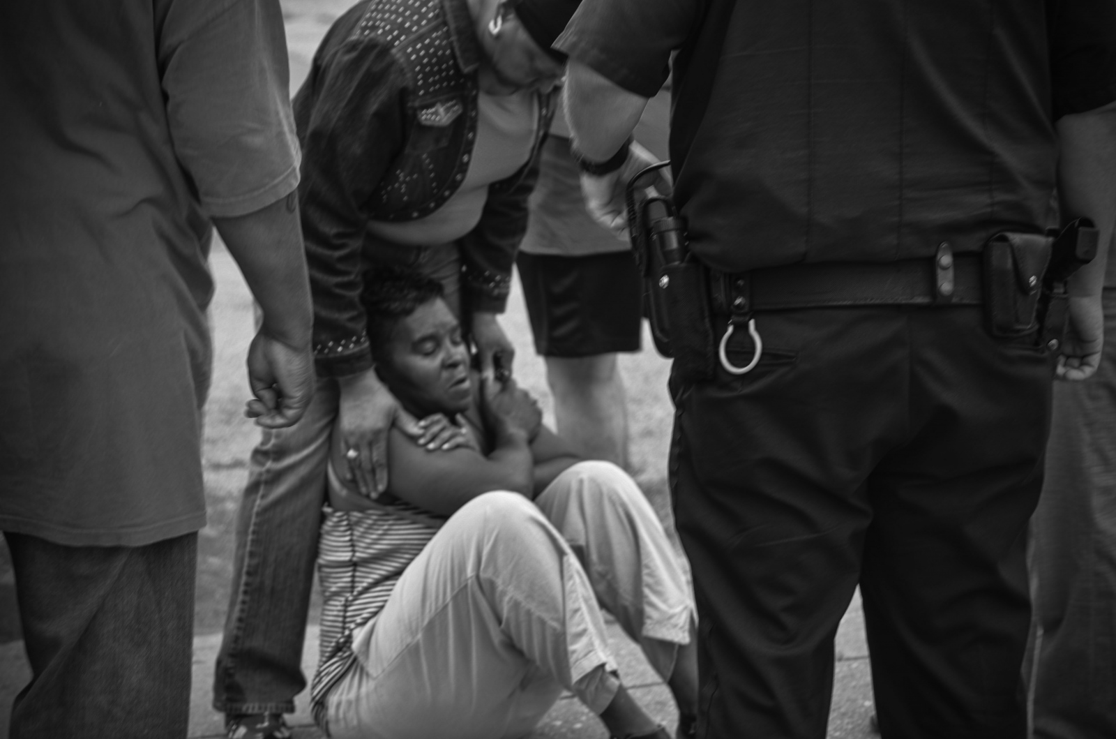 A woman drops to the ground on hearing that a man shot was not her son, who shared the same first name of the victim killed in the 3900 block of Hanover St. August 6, 2013.