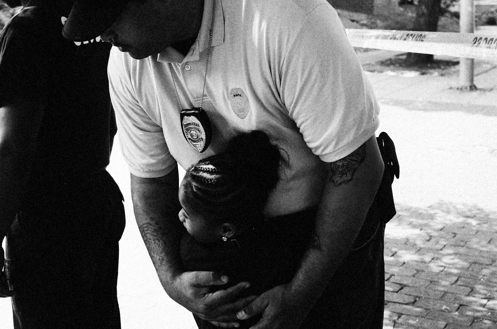 A young student runs into the arms of a Baltimore City School Police officer following a homicide across from her school in West Baltimore on August 12, 2013.