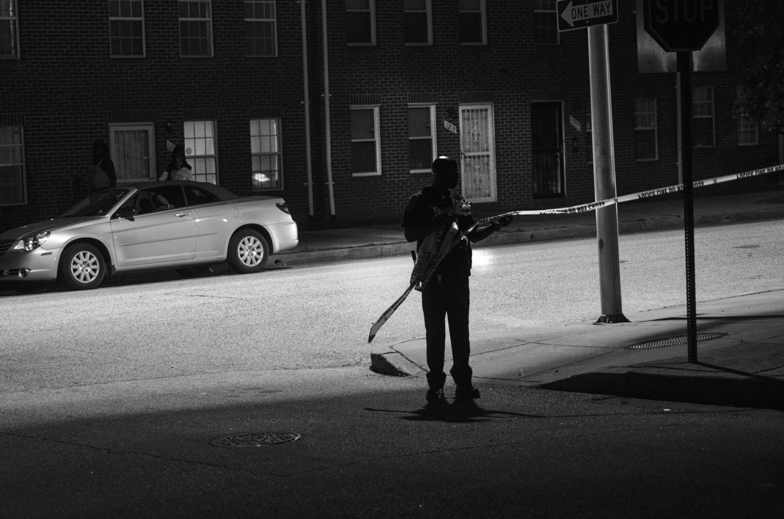 A police officer extends the crime scene at a shooting where a seven-year-old was killed at Eager Street and Central Avenue on August 17, 2013.