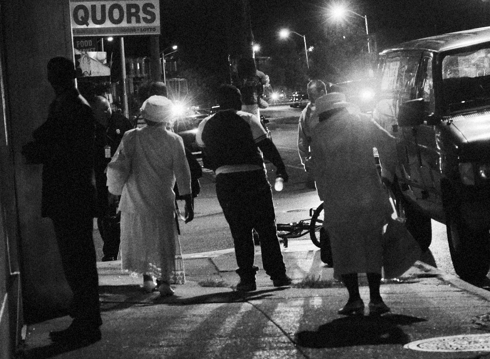 Late night church goers walk through a shooting scene in West Baltimore's Park Heights neighborhood on August 18, 2013.