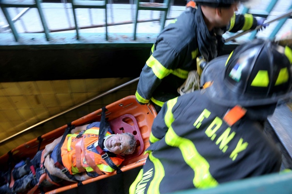 Firefighters rescue an MTA worker who fell on subway tracks while working on repairs at the 57th St. F train station in Midtown on Sunday morning.