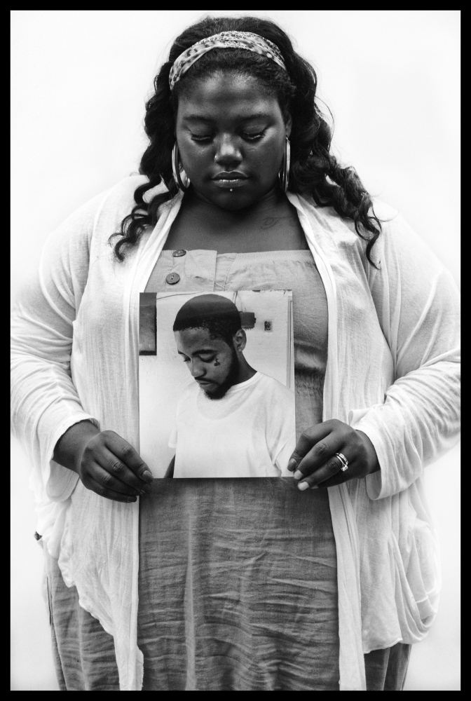 Dominique Ockimey holds a photo of her brother Davon who was gunned down in the 1400 block of Pimlico Road on July 2, 2013,
