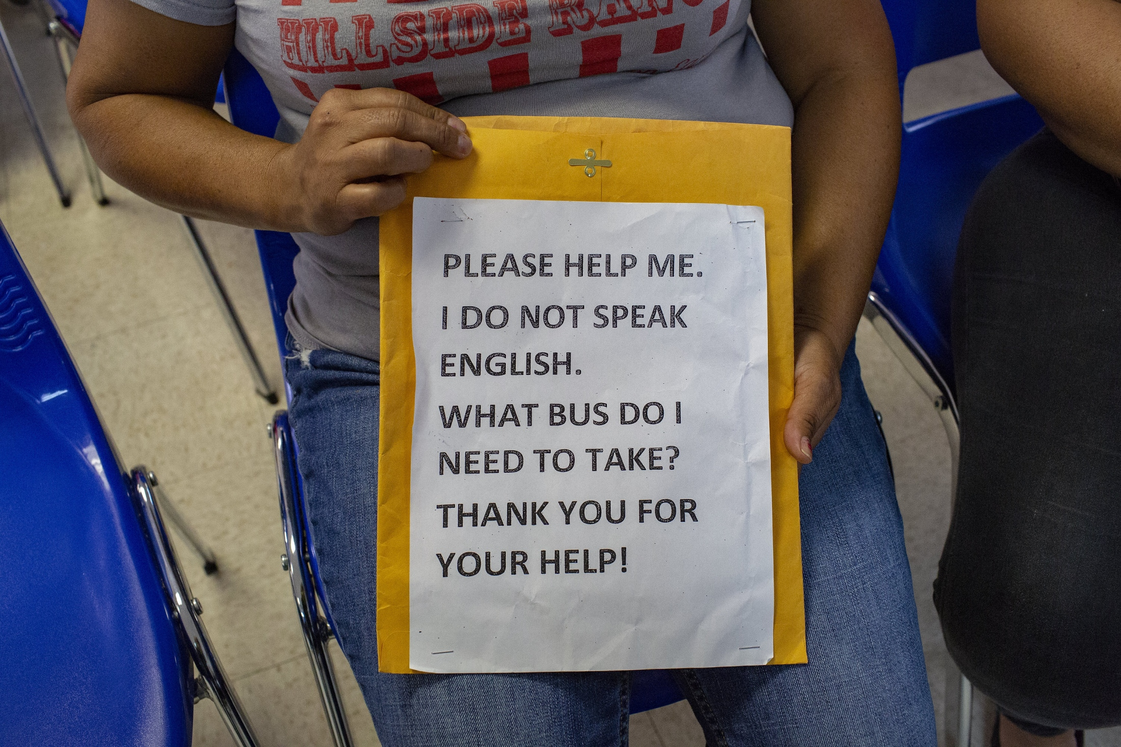 "I met a Central American migrant woman and her son from Catholic Charities in McAllen, Texas, who just got released from detention. The woman holds a sign that says "" Please help me I do not speak English."" This sign will help them as they travel across the U.S. to join other family members. (Kevin C Downs/Agence Cosmos)"