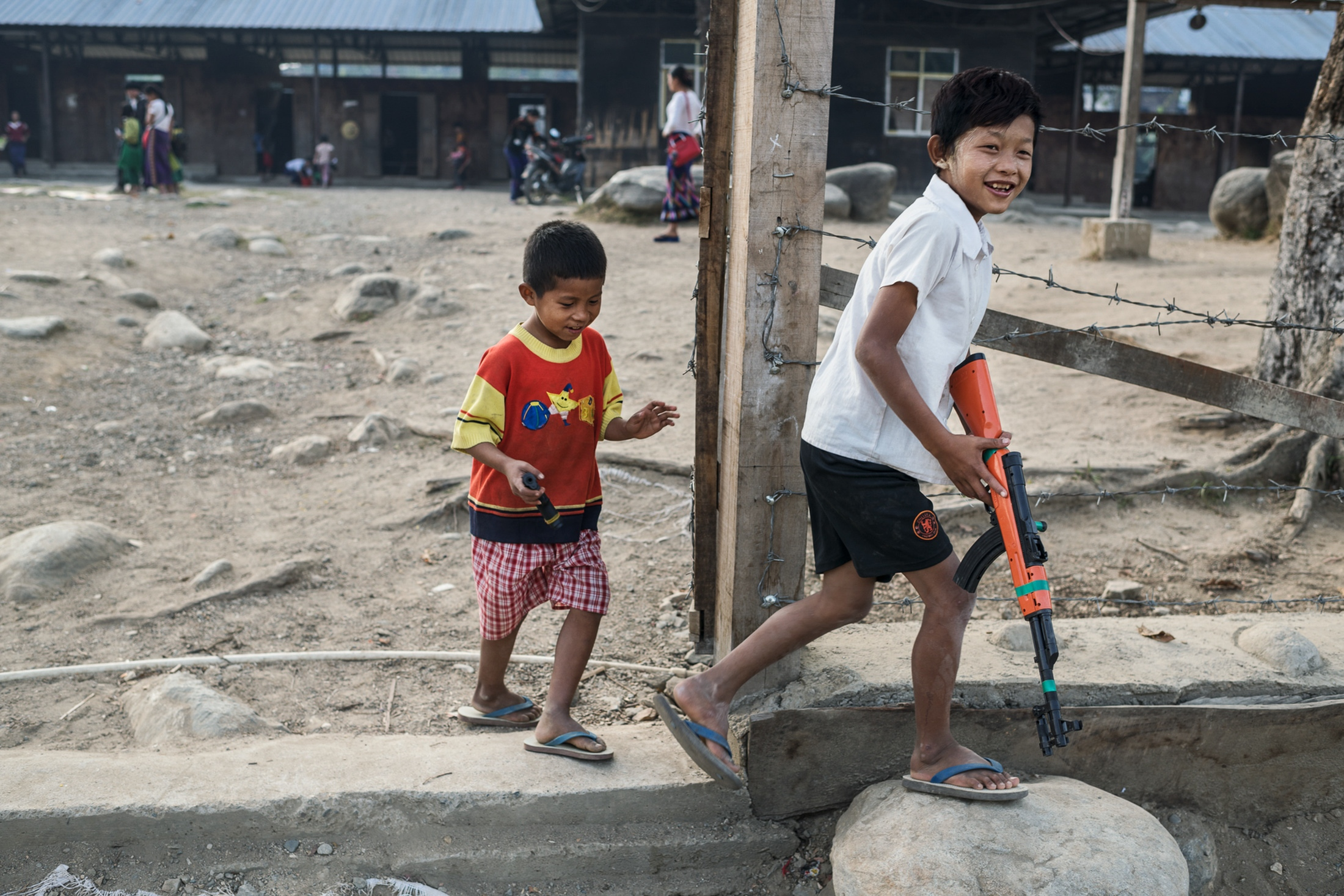 Children with toy guns play in the schoolyard at Je Yang IDP camp.