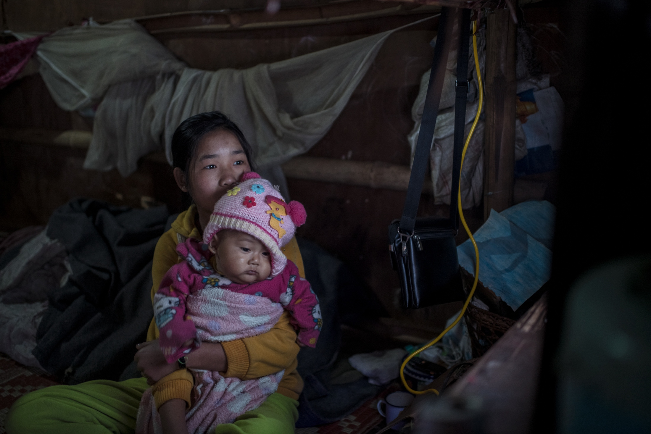 Bawk Ja, 15, and her baby cousin watching tv before school, in the Je Yang IDP Camp outside Laiza. The conflict have driven hundreds of thousands of people on the run, with several camps for Internally Displaced People (IDP) scattered along the border with China.