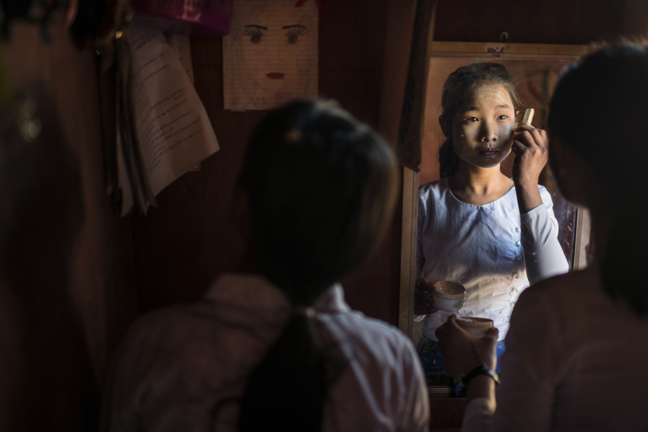 Nu Mai and Bawk Ja, 15, put on Thanaka during the school lunch break. Thanaka is a traditional cosmetic paste made from ground bark, used by women and girls all over Myanmar.