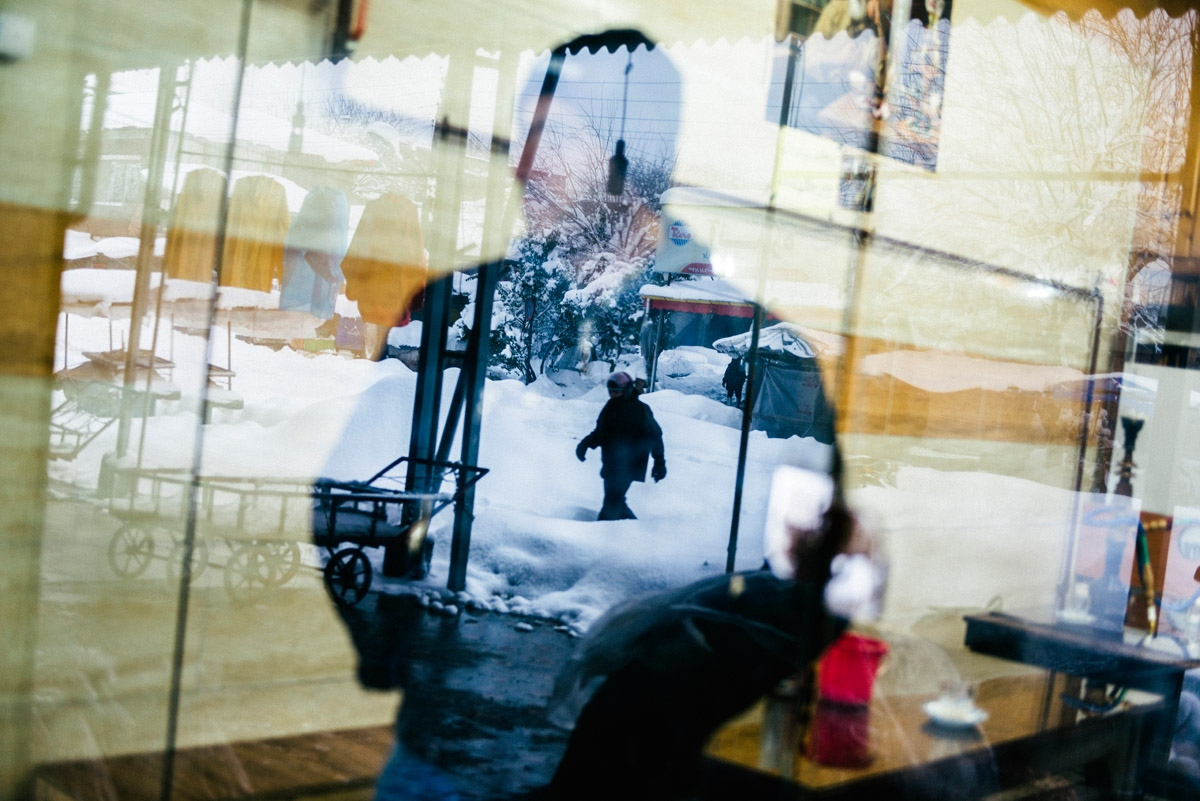 Two men are reflected from different sides of a window. For many migrants, the experience raises profound questions about their own identities. The process starts with that first and most consequential decision—whether or not to leave. Iran, 2015.