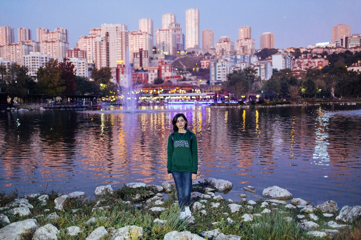 Helen my friend stands by the water in front of a cityscape. She's a migrant to Turkey and is in the process of applying for permanent residency. She says living here provides her with a peace of mind she couldn't enjoy back home. Turkey, 2017.