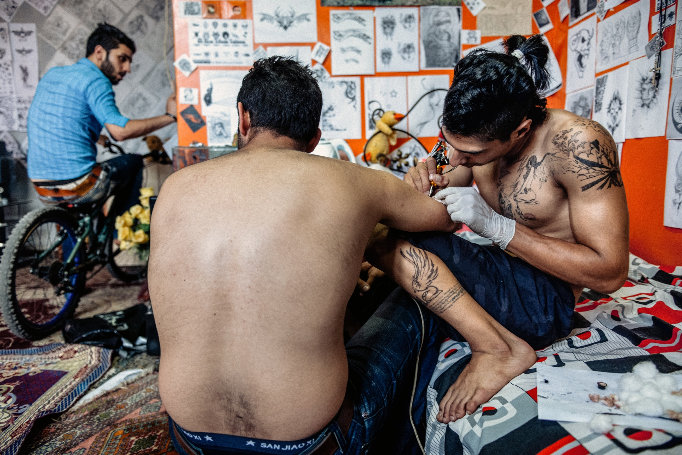 "Tattooing is one of the elements that their so-called ""Gang Style"" signature is. Tattooing is one of the ways which Farshid could earn money. His own room is the place which he uses for this business. Rasht, Iran, Jul 2014."