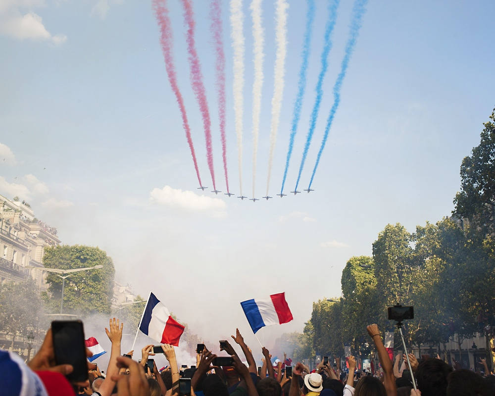 Air planes flew over the Champs Elysée avenue in Paris while the french football team went down the avenue on their bus.