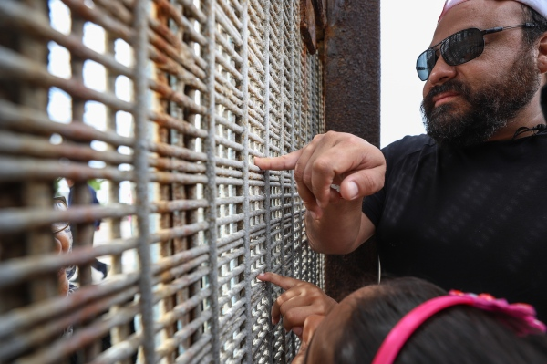 Human touch through a fence at the US/Mexico border.