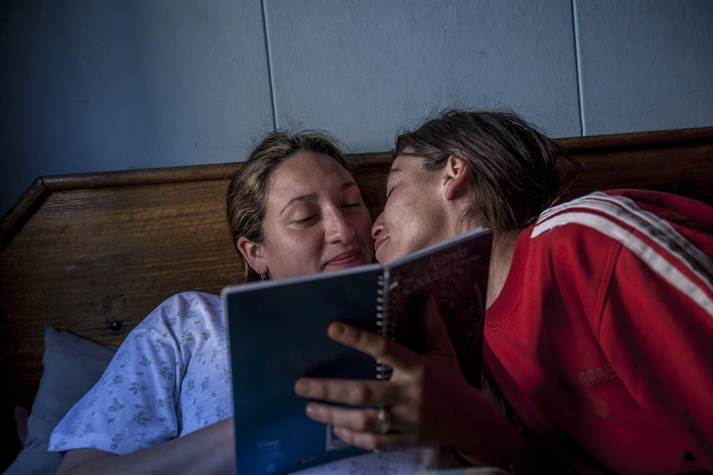 Karen kisses her girlfriend Mariel while they reads an old Mariel's journal. Santiago,Chile. 2010