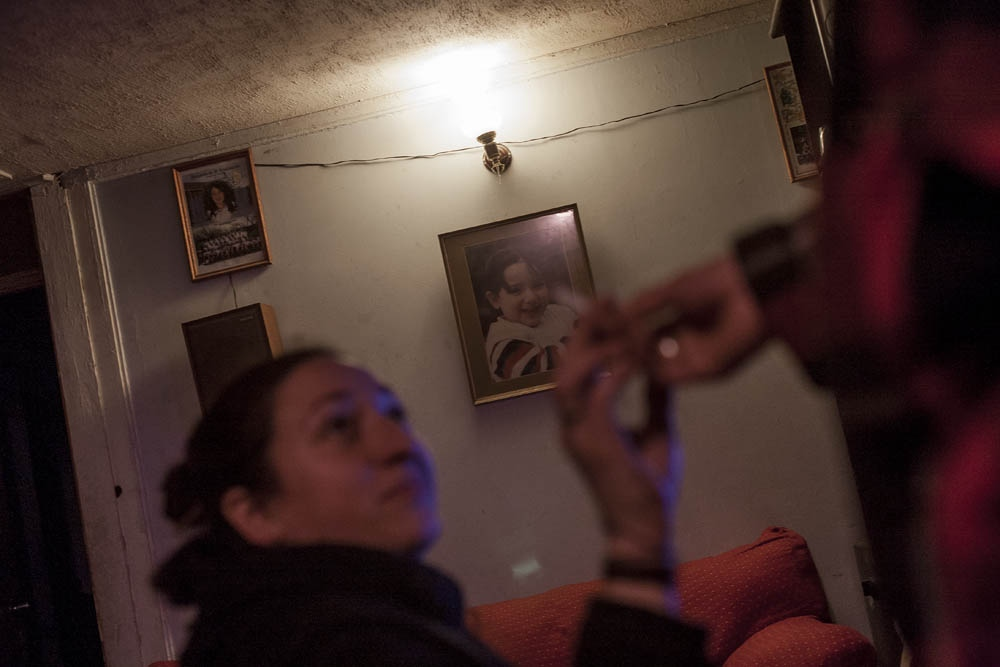 Mariel receives a tobacco cigar from Karen. On the background hangs a portrait of Mariel's daughter, Yara. Santiago, Chile.2011