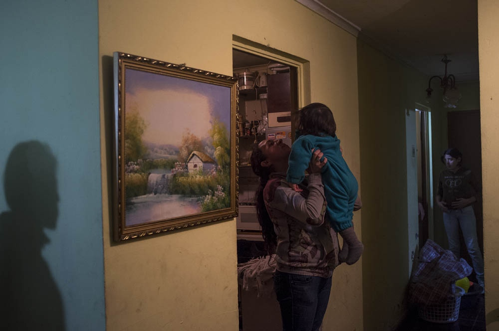 Mariel lifting a niece at her mother house. Karen's shadow on the left and Yara on the right.Santiago, Chile. 2013