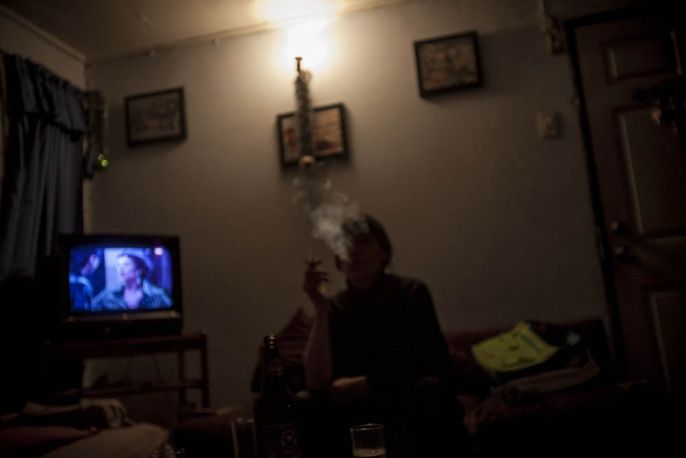 Karen smokes a cigar in her living room. Santiago, Chile.