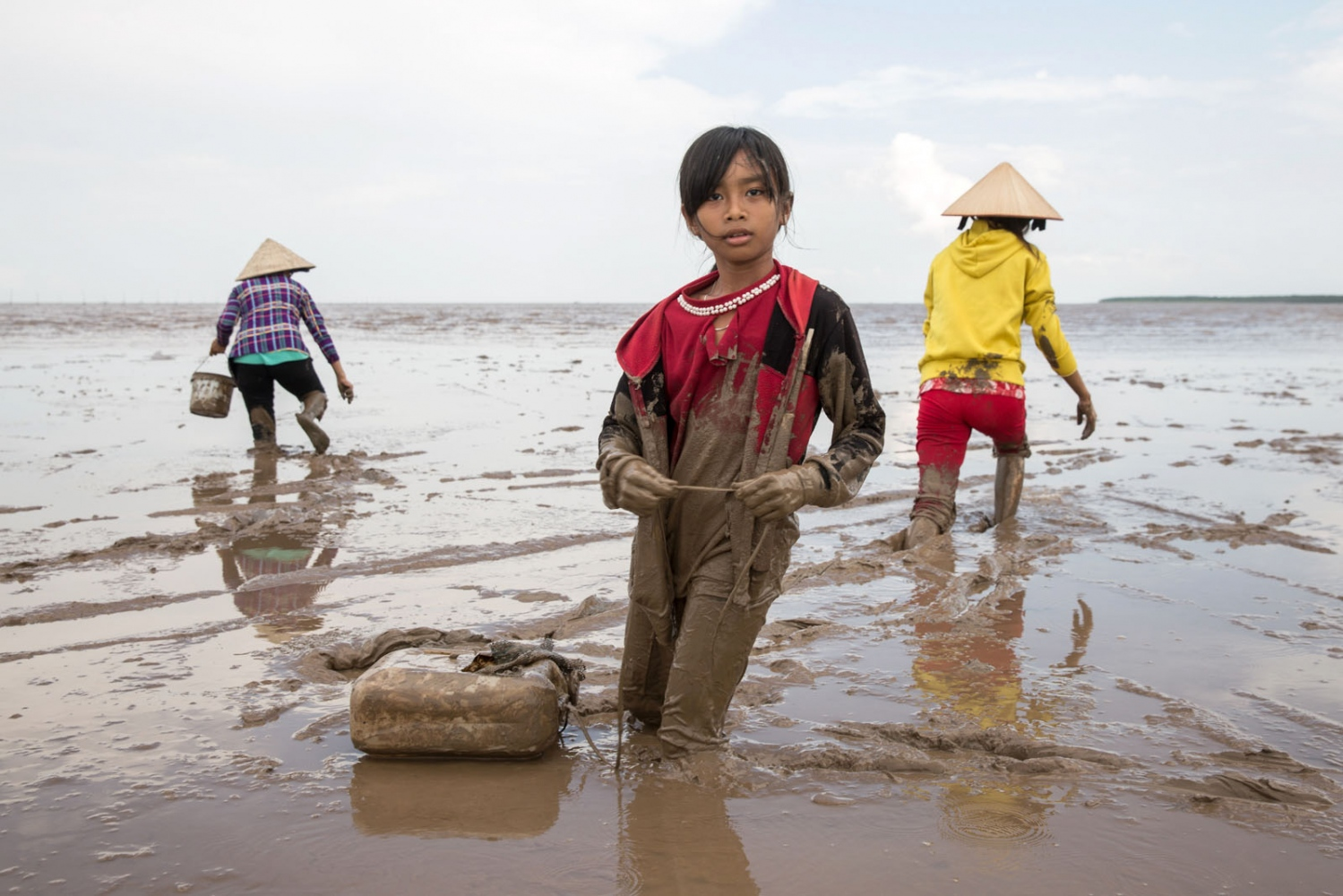 A young girl helps her family collect snails during low-tide in Southern Soc Trang Province. These mangroves were destroyed completely by bombing during the Vietnam War but over the last 25 years were able to grow back naturally, finally being protected and expanded by Government initiatives. Now, over 20 families come to the beach daily to collect snails and other fish that returned with the healthy mangrove eco-system.