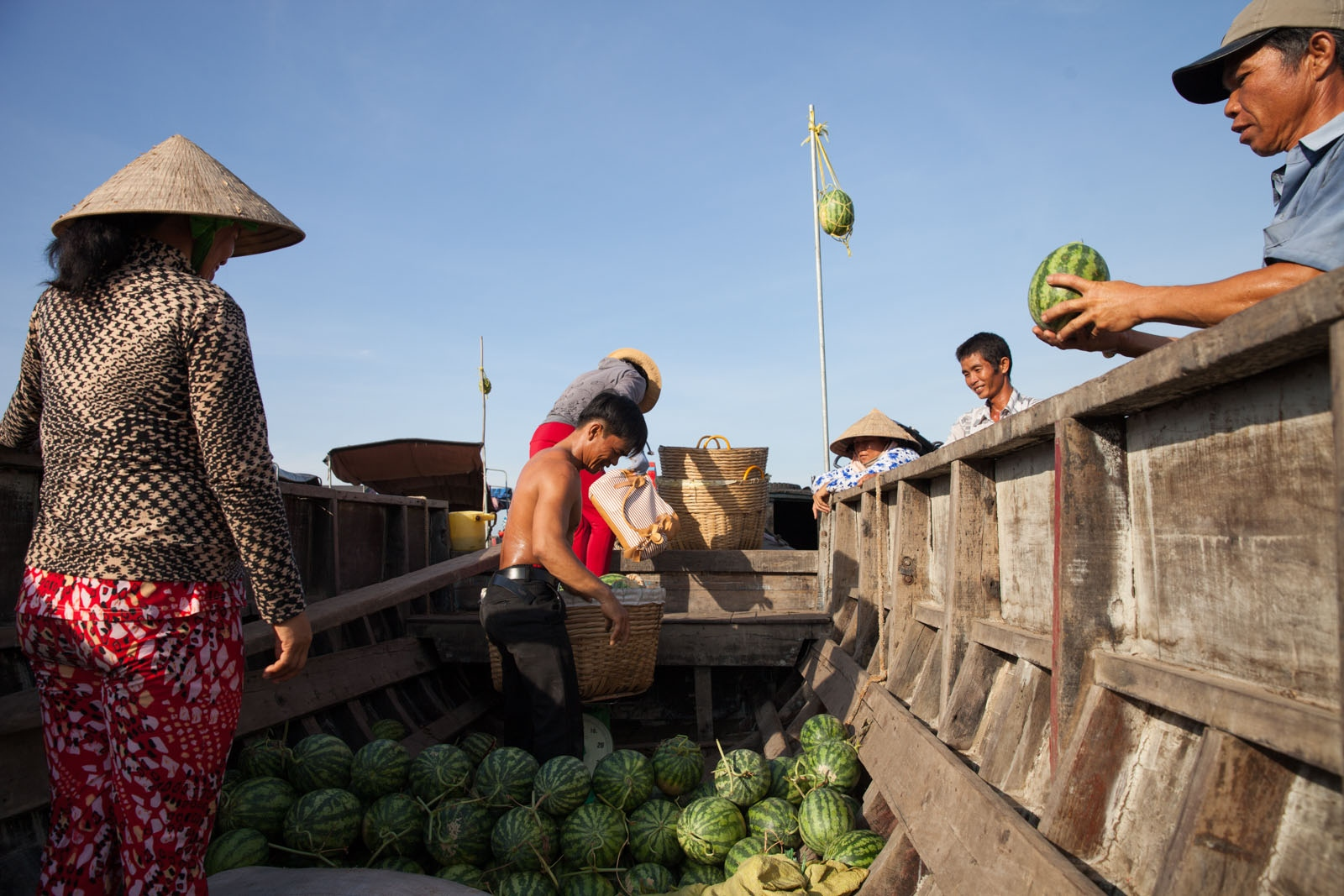 On a boat moored to a river bank customers come to purchase watermelons that have been brought downstream from the owners farm.