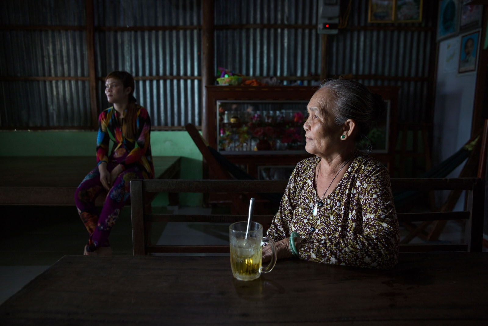 Nguyen Thi Chep, 70, sits in her house with her daughter Than Thi Ut. Both her husband and son were killed when Typhoon Linda devastated Southern Vietnam in 1997 but only the body of her 13 years old son was retrieved, her husband's body was never found. Believed to be the worst typhoon in at least one hundred years to hit Vietnam, thousands were killed and huge areas completely destroyed. Her family were fisherman living in Song Doc town that is one of the most remote communities in the Delta. After the Typhoon hit Red Cross workers had to travel by riverboat to bring aid to the 150,000 most affected people, due to the lack of roads.