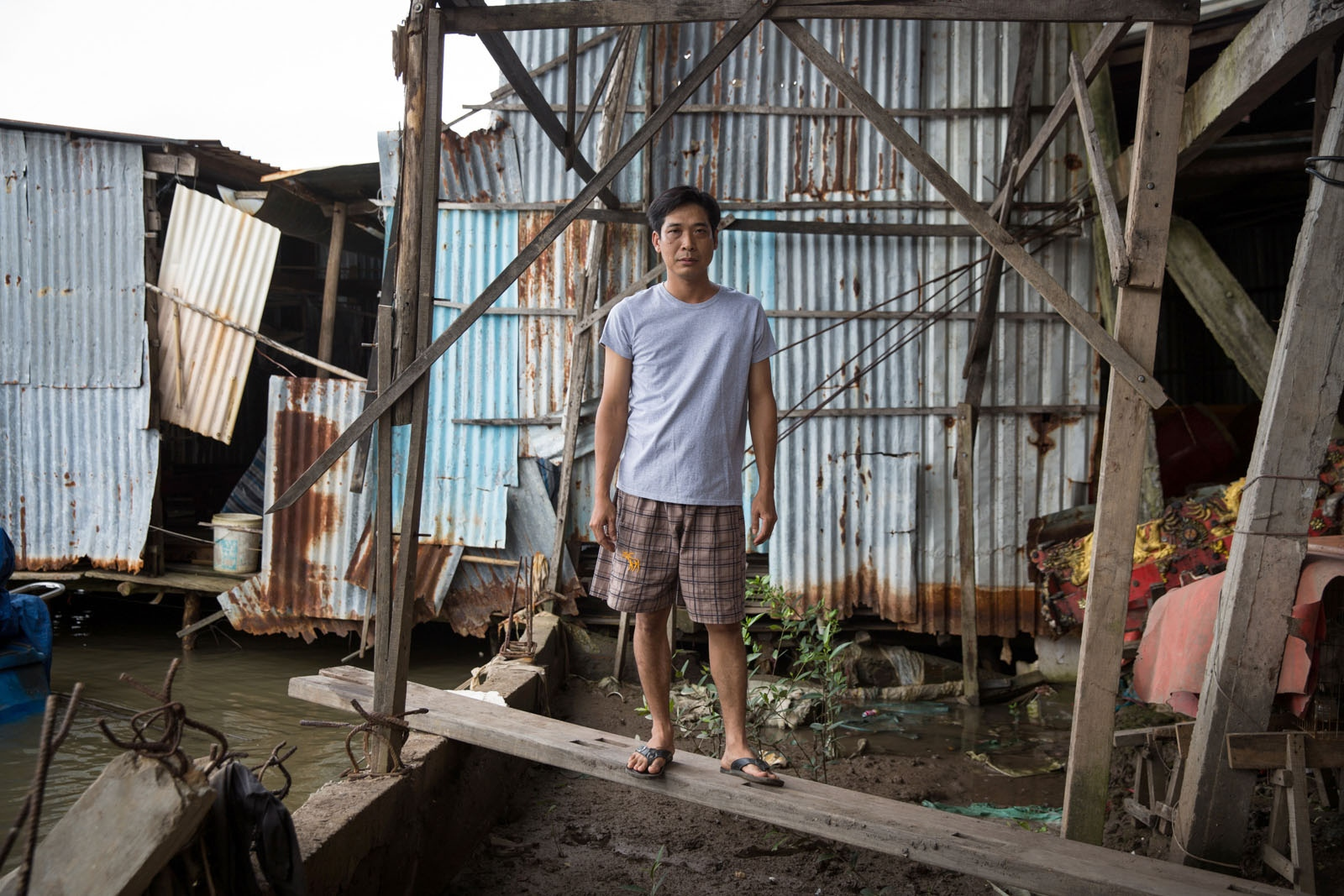 Truong Minh Thnan, 36, stands in part of his family house in Nam Can town which has collapsed in to the Kinh Tac River. His family-run business manufacturers coffins and they use the river to transport the heavy wooden coffins to customers. He said the problem of erosion began in 2006 and severely affects 47 communities in this district alone. Despite laying a foundation of two meters of cement under his house and placing steel-reinforced cement supports 30 meters down, it is still unstable.
