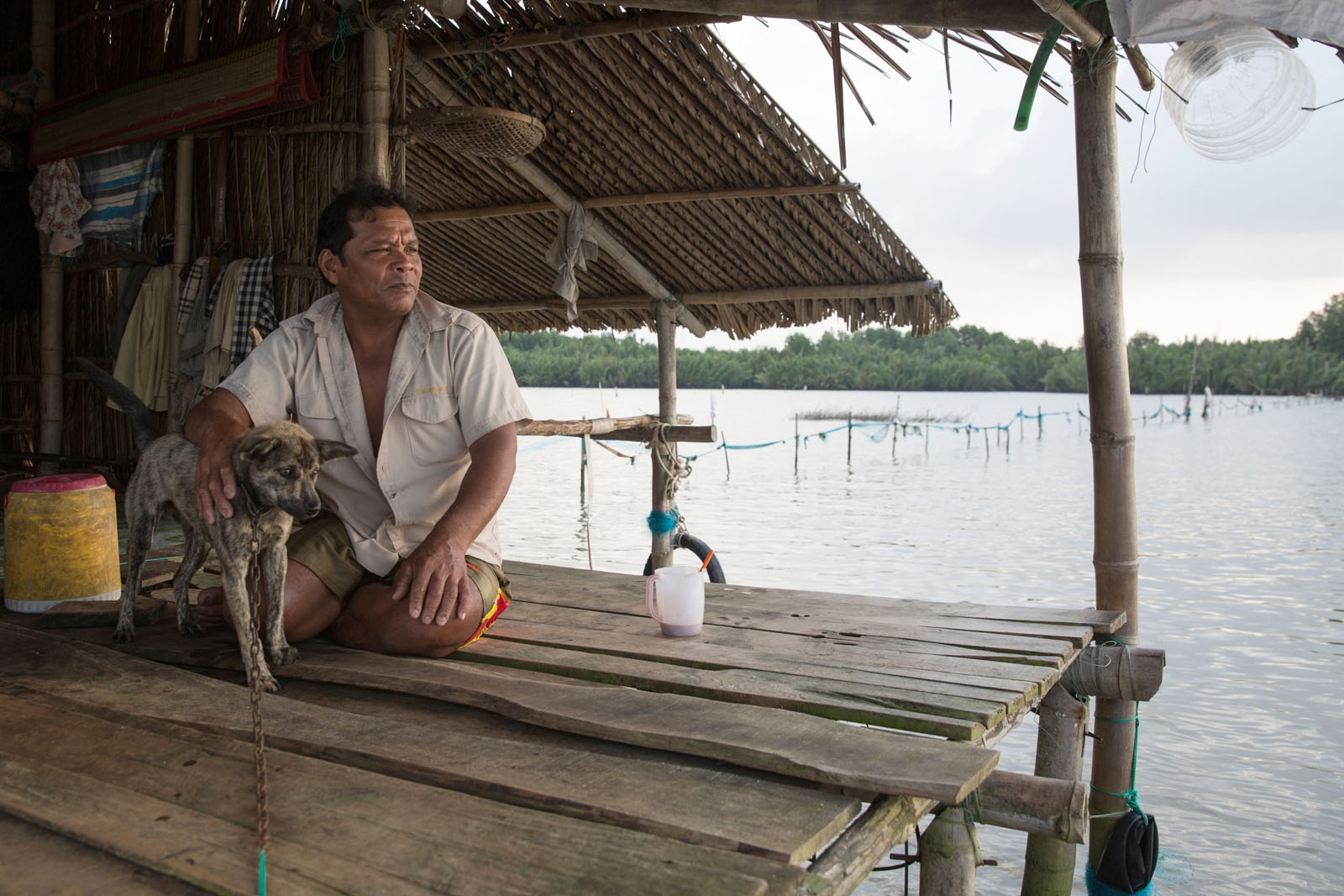 Nguyen Van Chien, 50, sits on his stilted house in the middle of Thi Tuong Lagoon with his trusted guard dog. With the quantity of fish caught in the lake reduced by 3x in the last decade he invested in growing clams. They can be harvested only once a year because the gestation period lasts 9 to 10 months but he can sell them for approximately US$35/kg for large ones and US25/kg for smaller ones. One of the main causes he believes that is responsible for the reduced fish stocks is the fertiliser run-off from nearby shrimp farms that pollute the lake.
