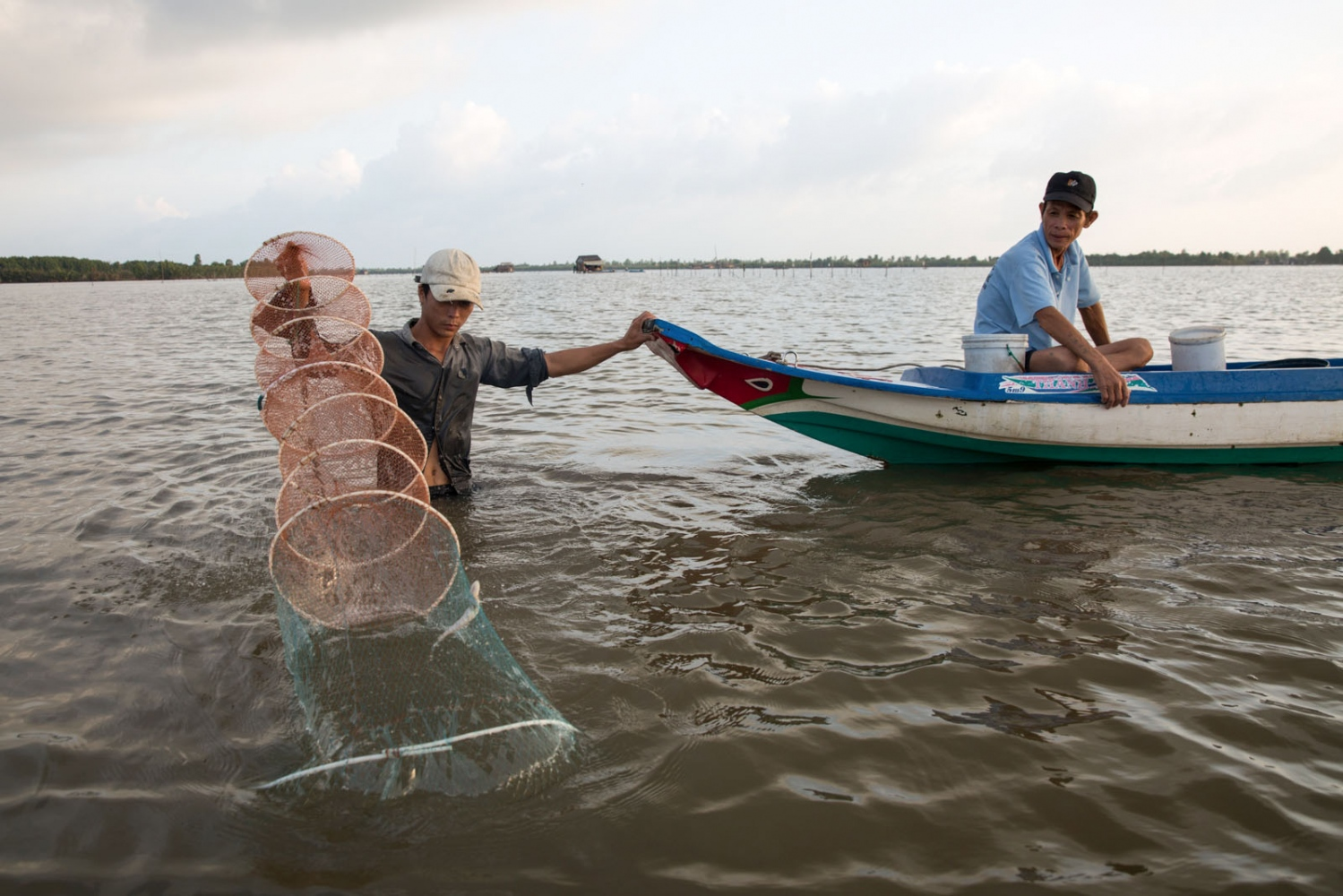 Two men check their nets at dawn on Thi Tuong Lagoon in Ca Mau Province. 2km wide and over 10km long it is the largest natural lagoon in the Delta and is home to hundreds of households who for generations have completely relied on the lagoon's marine resources for their subsistence. But now, everything has been changing rapidly. The visible rises in sea level and temperature have caused changes in the lagoon's natural flooding process. Normally, the lagoon is influenced by daily tidal effects and during the high tide adult marine life like fish and crabs from the sea migrate to hunt in lagoon. But during the low tide, larvae and juveniles are born and grown making it a perfect sanctuary for many marine species. However, in recent years, local farmers have witnessed more frequent flooding in the lagoon meaning that the high tide is increasingly high, leaving little space for a tidal mud flat where baby shrimp and crab can grow.