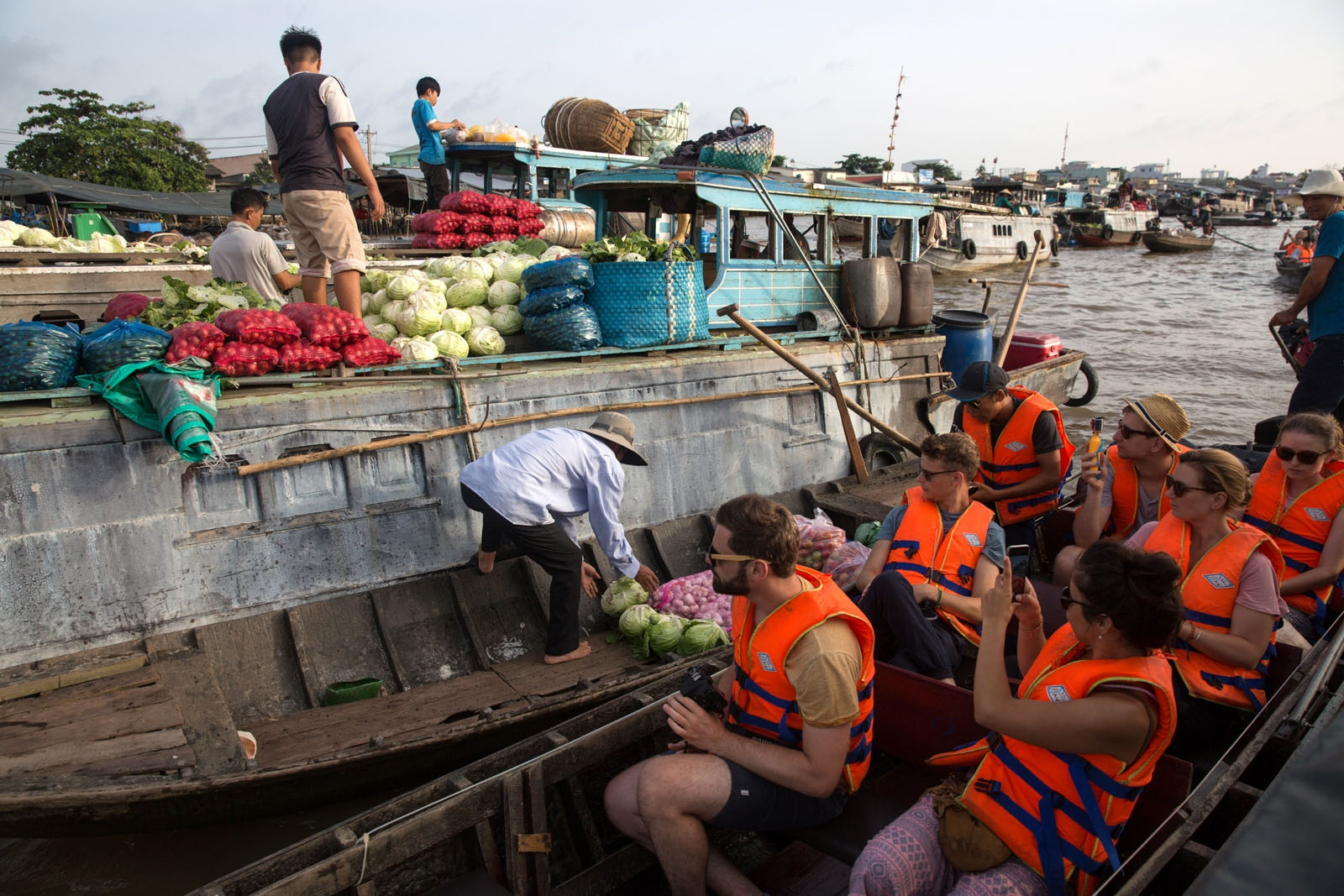 Foreign tourists take photographs of the activities at Cai Rang floating market in Can Tho city. Cai Rang is the largest floating market in the Mekong Delta but due to improved infrastructure in the form of roads and bridges the market is slowly declining as vendors prefer the speed and availability of roads. Now tourist boats almost out-number the house boats selling vegetables and fruit.