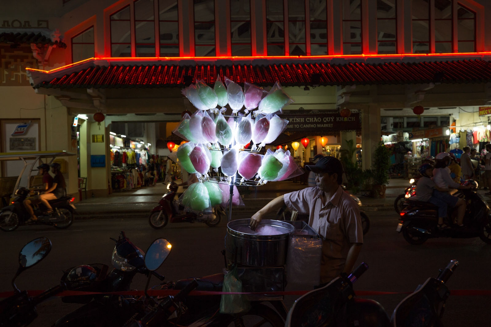 At an evening food market in Can Tho city a man sells cotton-candy to tourists and locals.